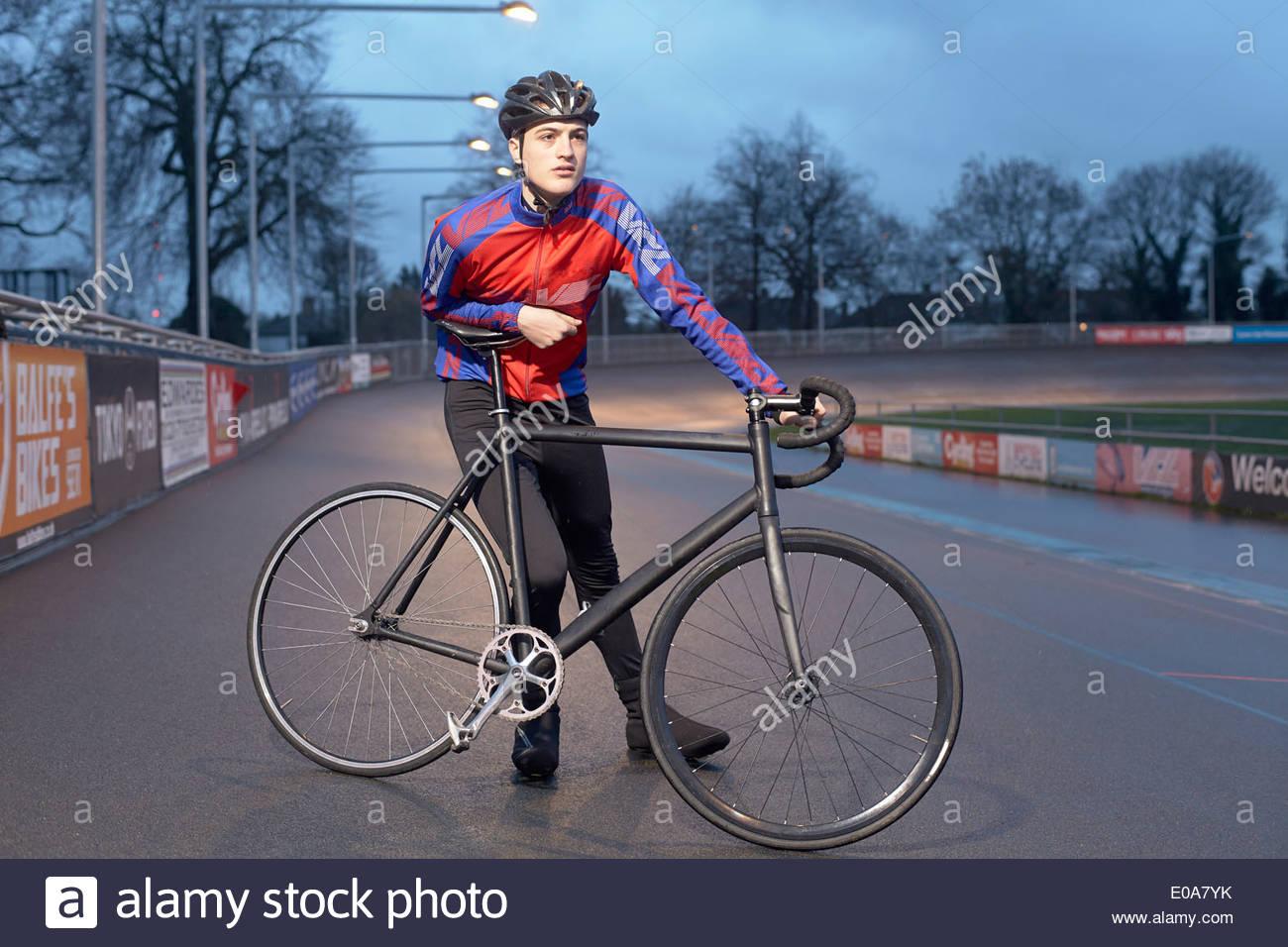 Ritratto di giovane maschio ciclista con ciclo al velodromo di notte Immagini Stock