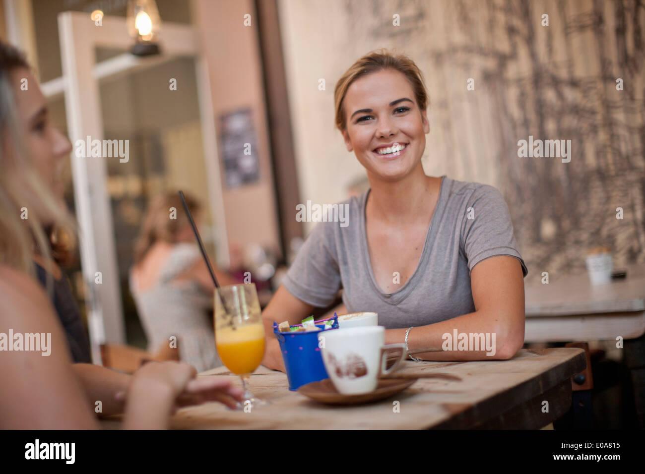 Due giovani femmina adulta amici godendo di una sessione di conversazione testuale in cafe Immagini Stock