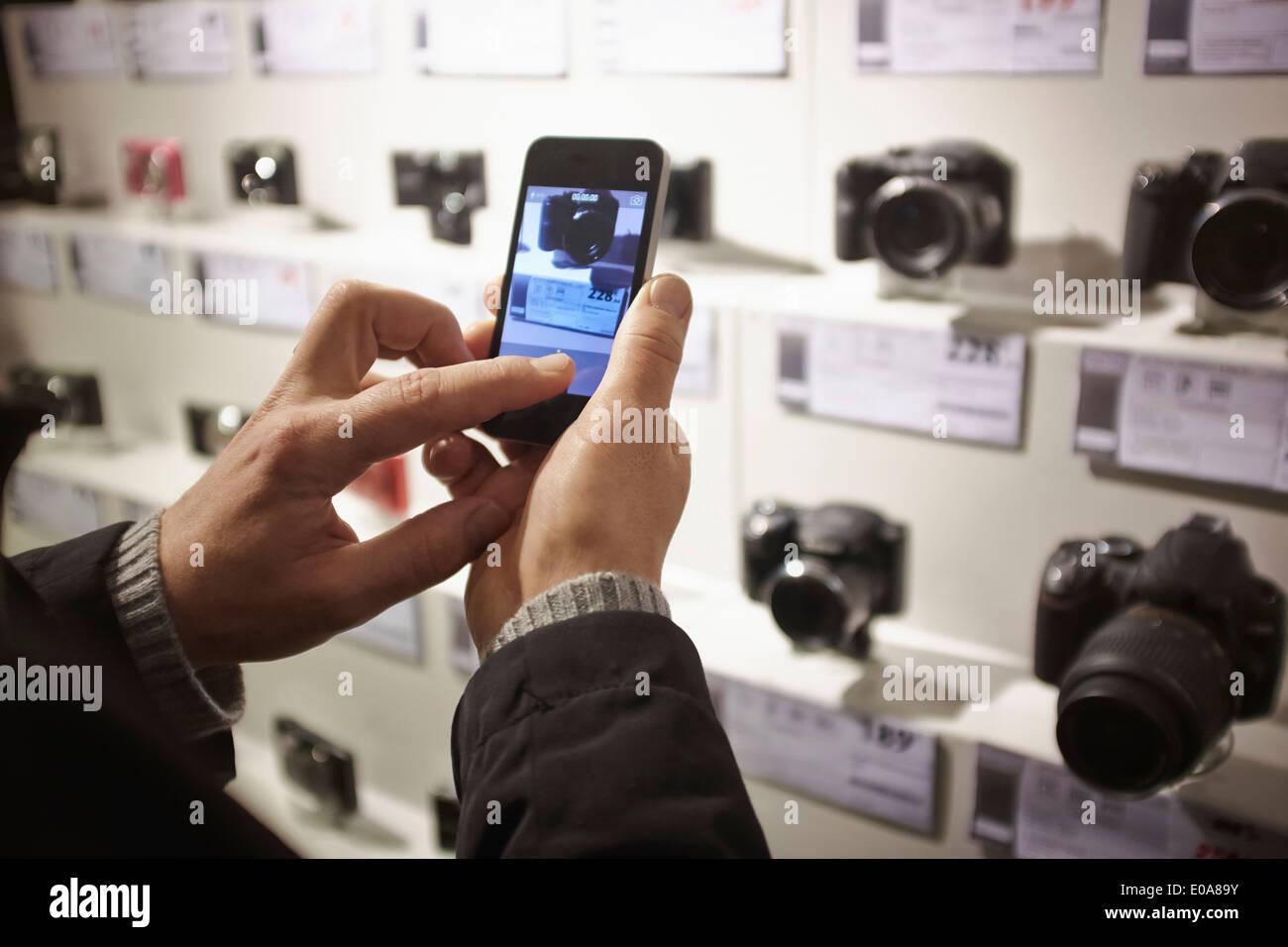 Metà uomo adulto fotografare la fotocamera in negozio il display utilizza lo smartphone Foto Stock