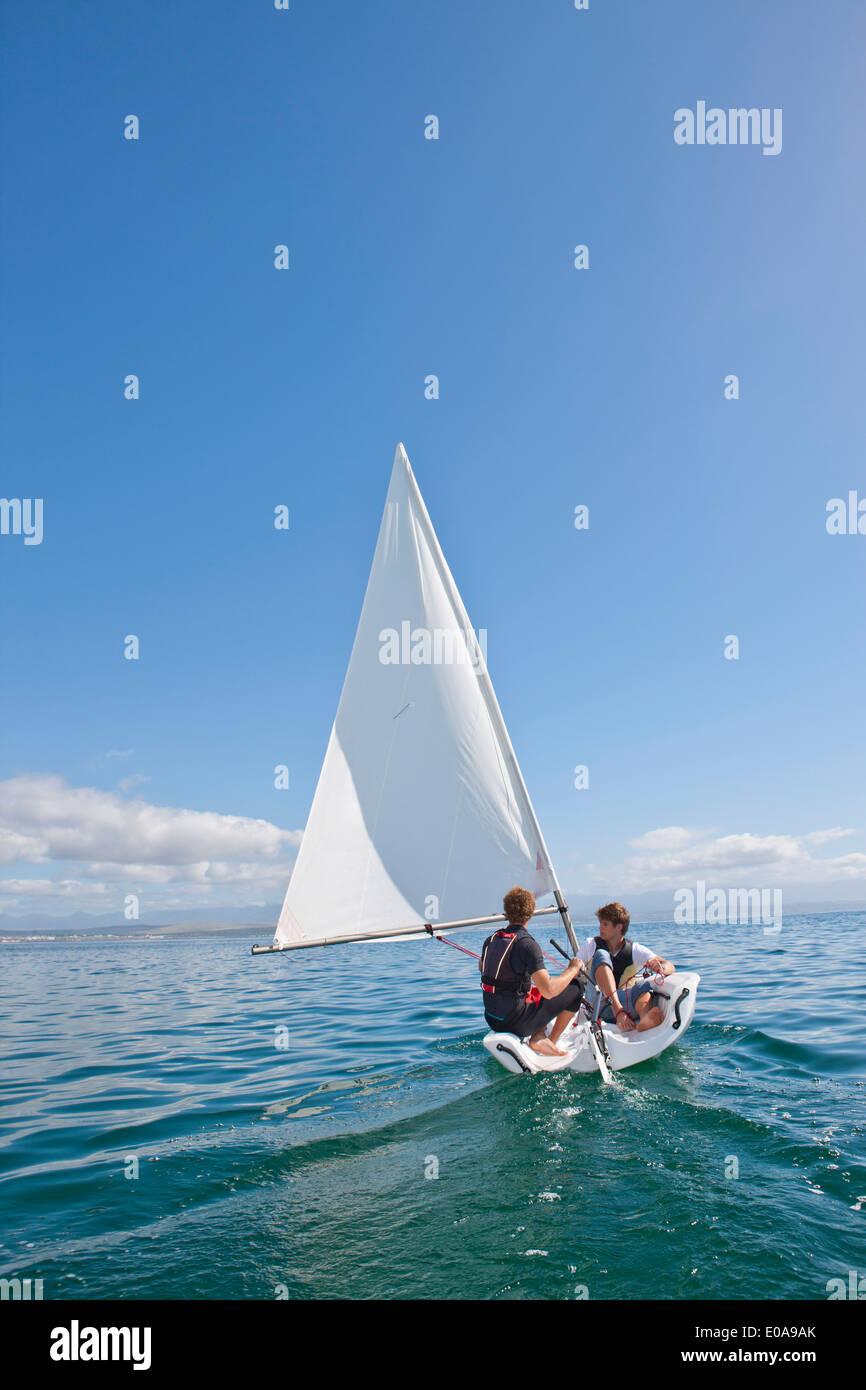 Due giovani uomini di veleggiare in mare Immagini Stock