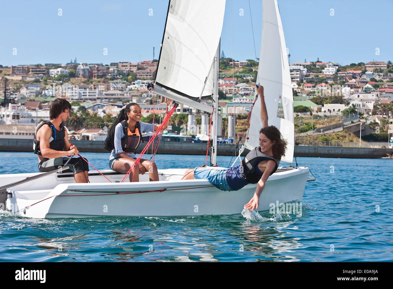 Tre giovani amici vela in porto Immagini Stock
