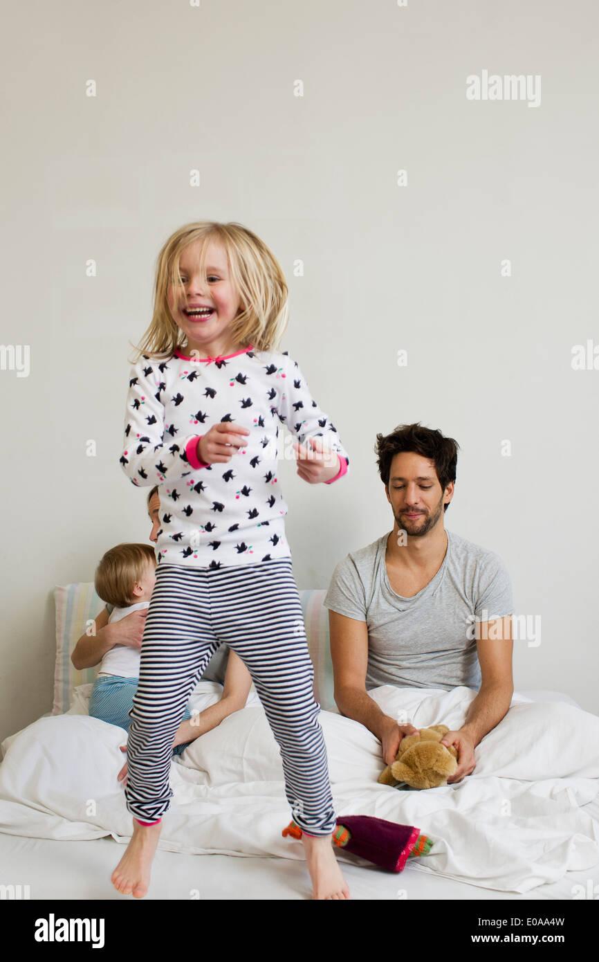 Ragazza giovane di saltare sul suo letto dei genitori Immagini Stock