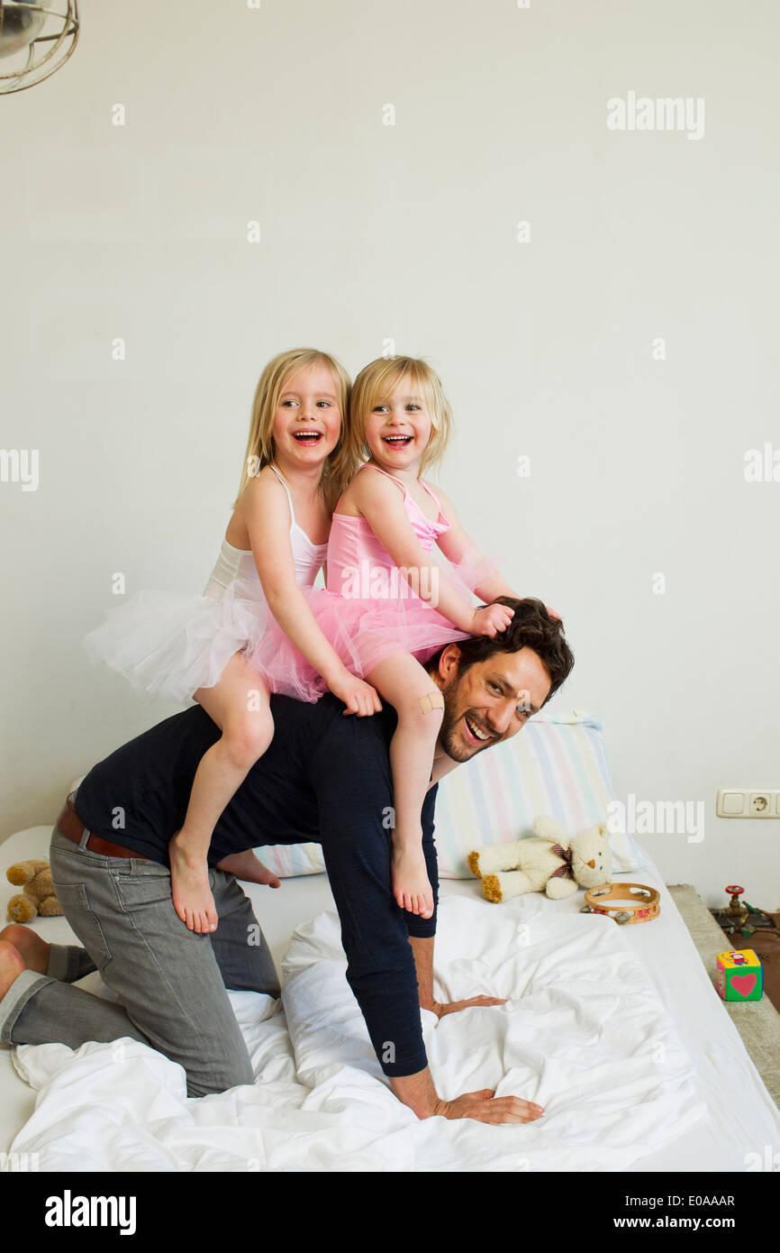 Ritratto di metà adulto padre dando due giovani figlie di un piggy back Immagini Stock