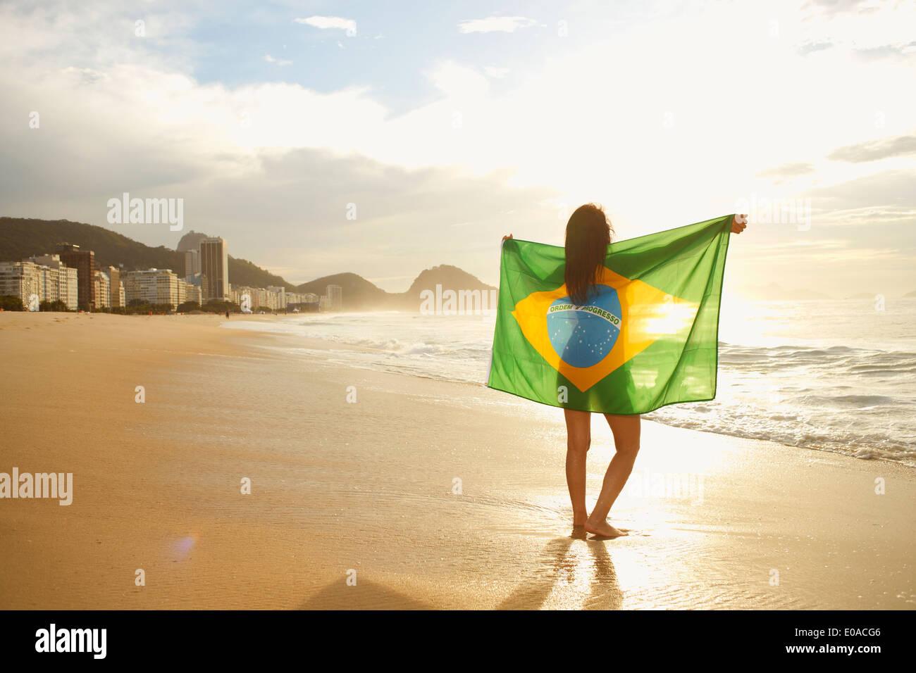 Donna che mantiene bandiera brasiliana sulla spiaggia di Copacabana, Rio, Brasile Immagini Stock