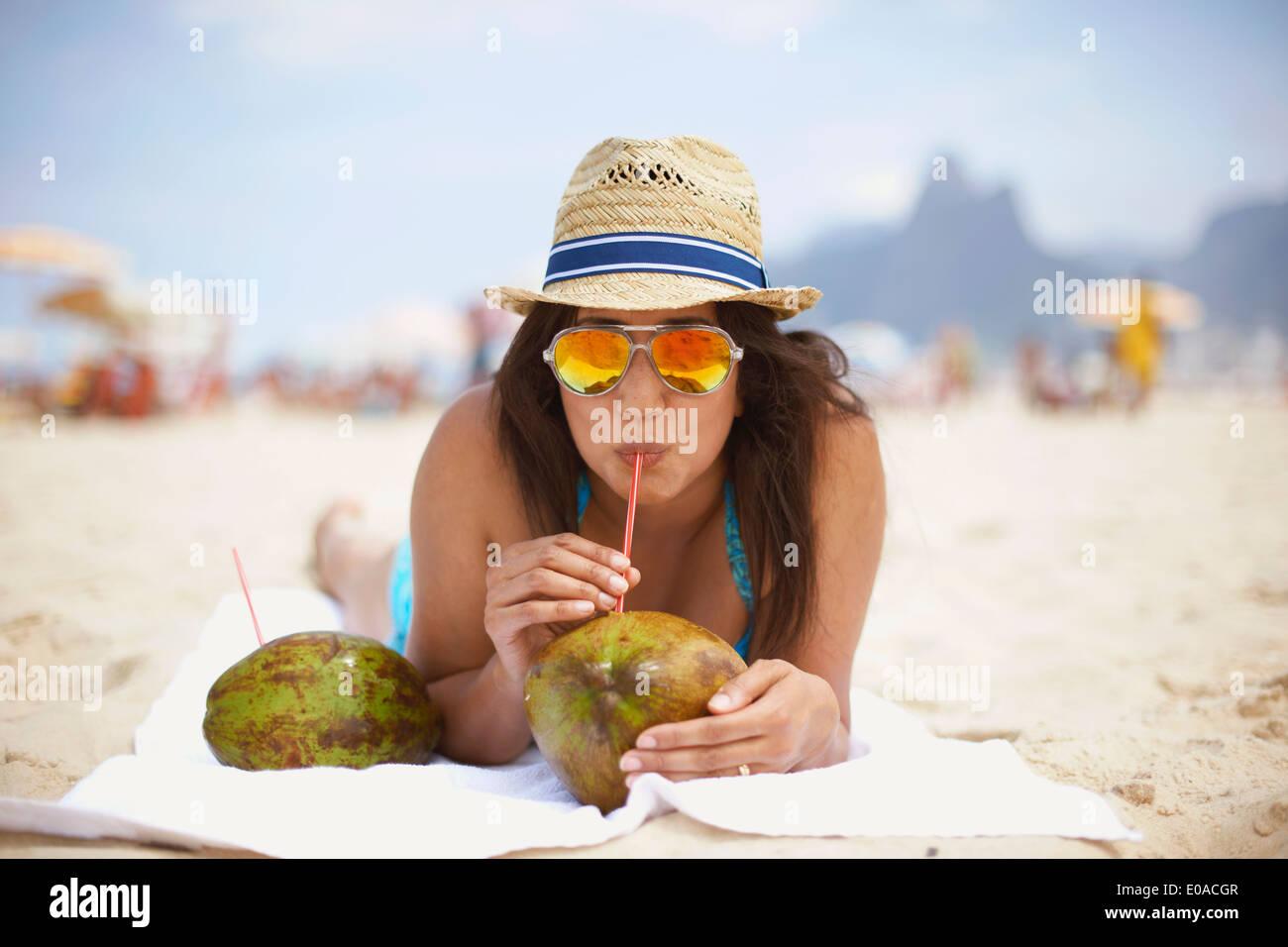 Ritratto di donna matura di bere da noce di cocco, la spiaggia di Ipanema, Rio de Janeiro, Brasile Immagini Stock