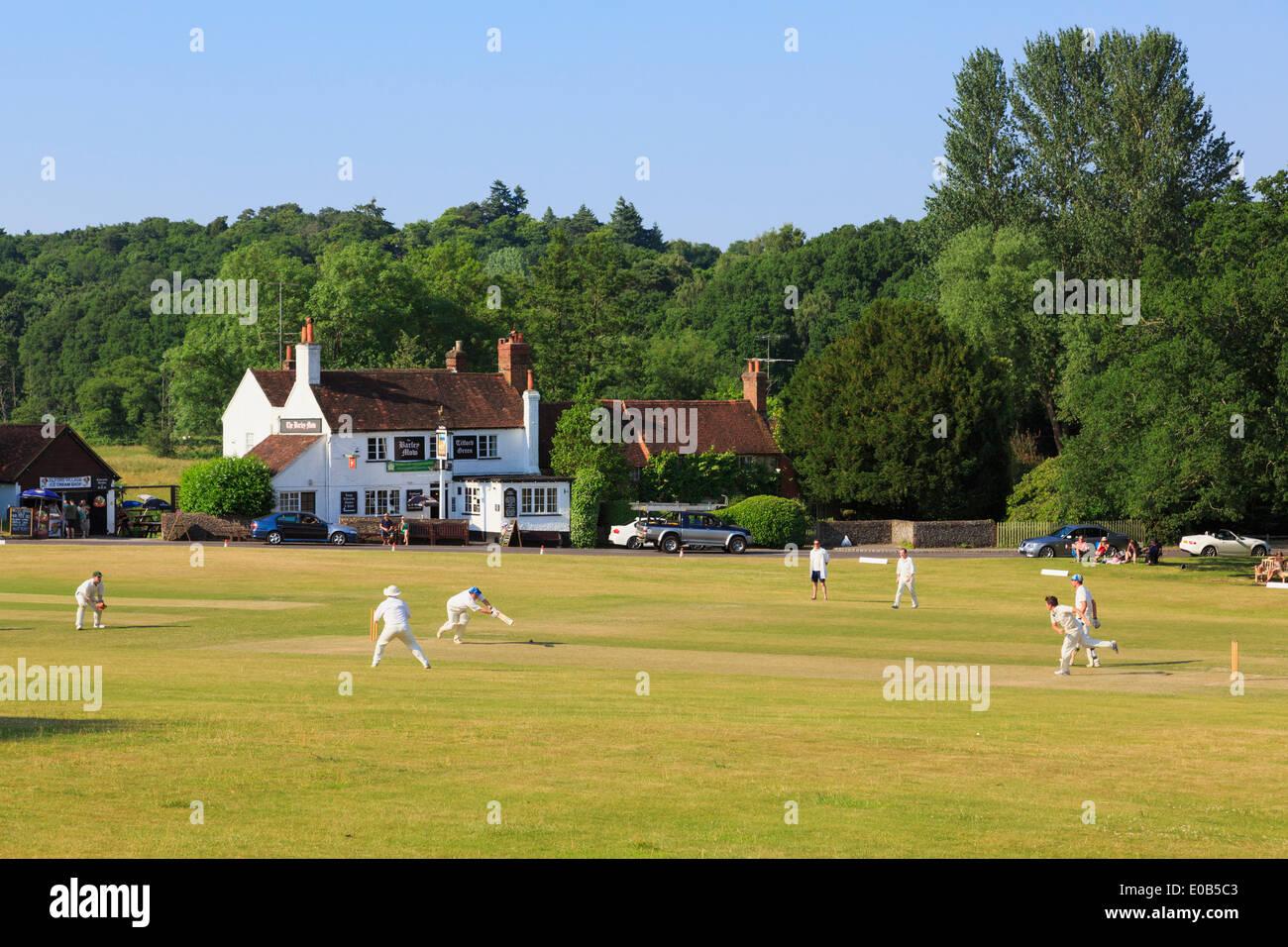 Le squadre locali giocando una partita di cricket sul villaggio verde nella parte anteriore di orzo Mow pub in una sera d'estate. Tilford Surrey in Inghilterra REGNO UNITO Immagini Stock