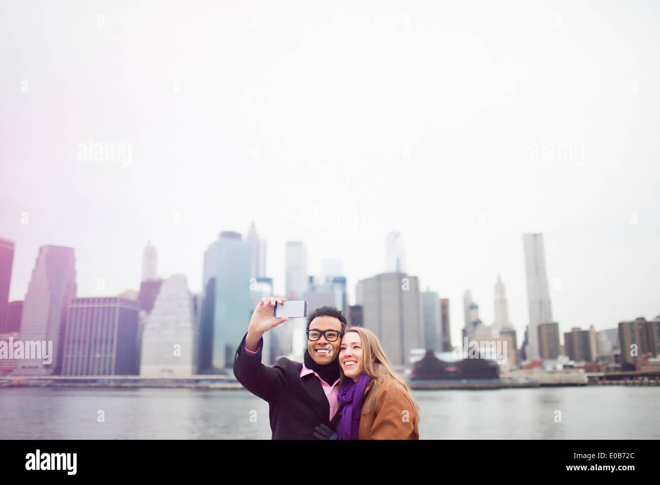 Coppia giovane tenendo selfie con lo skyline di Manhattan, New York, Stati Uniti d'America Immagini Stock