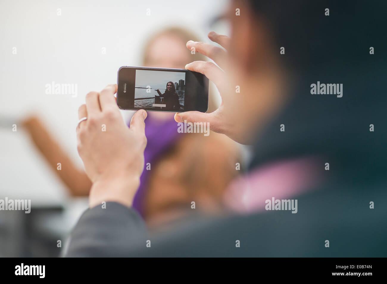 Chiusura del giovane di fotografare la ragazza sul telefono con fotocamera Immagini Stock