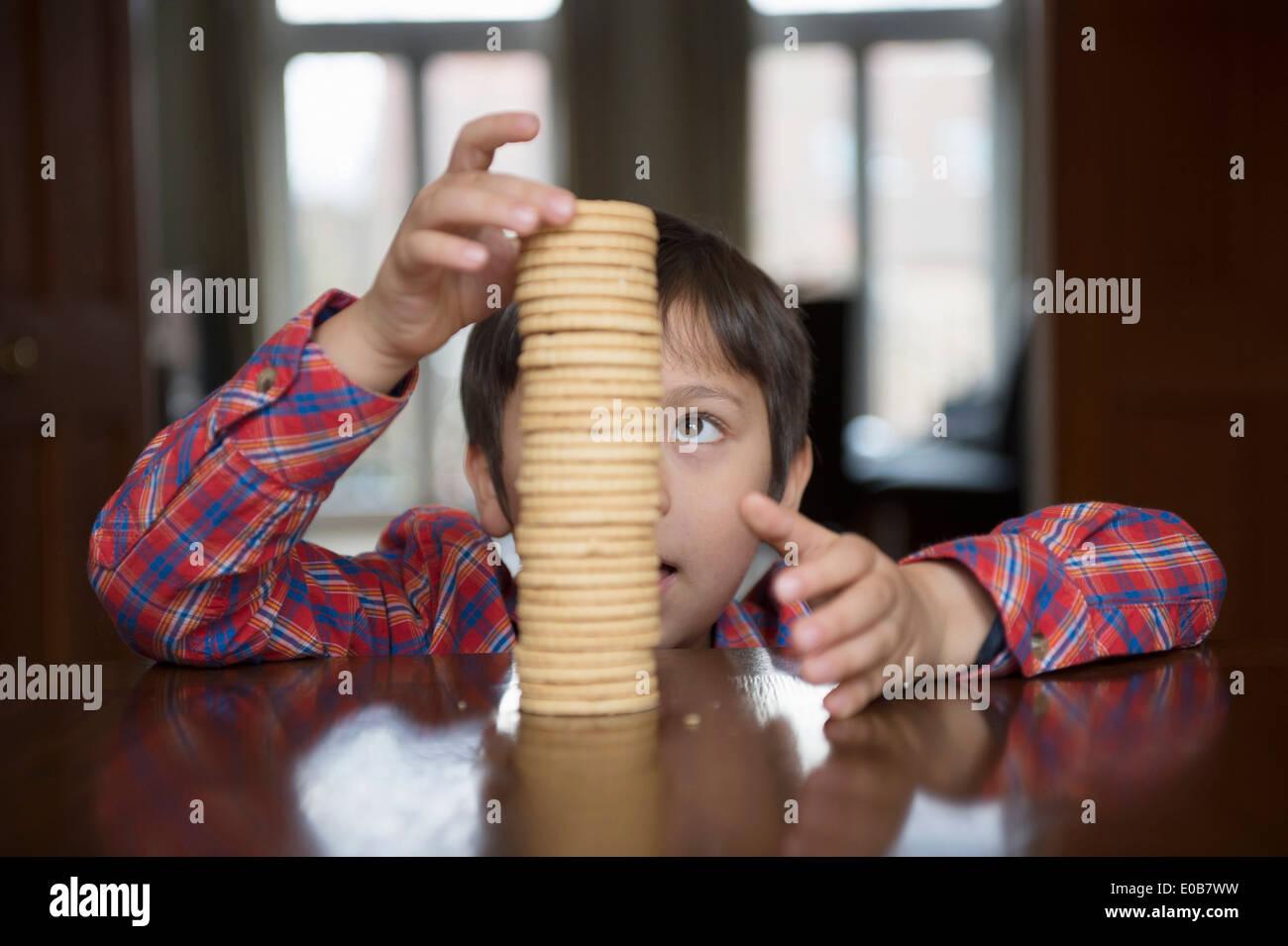 Ragazzo impilando biscotti Immagini Stock