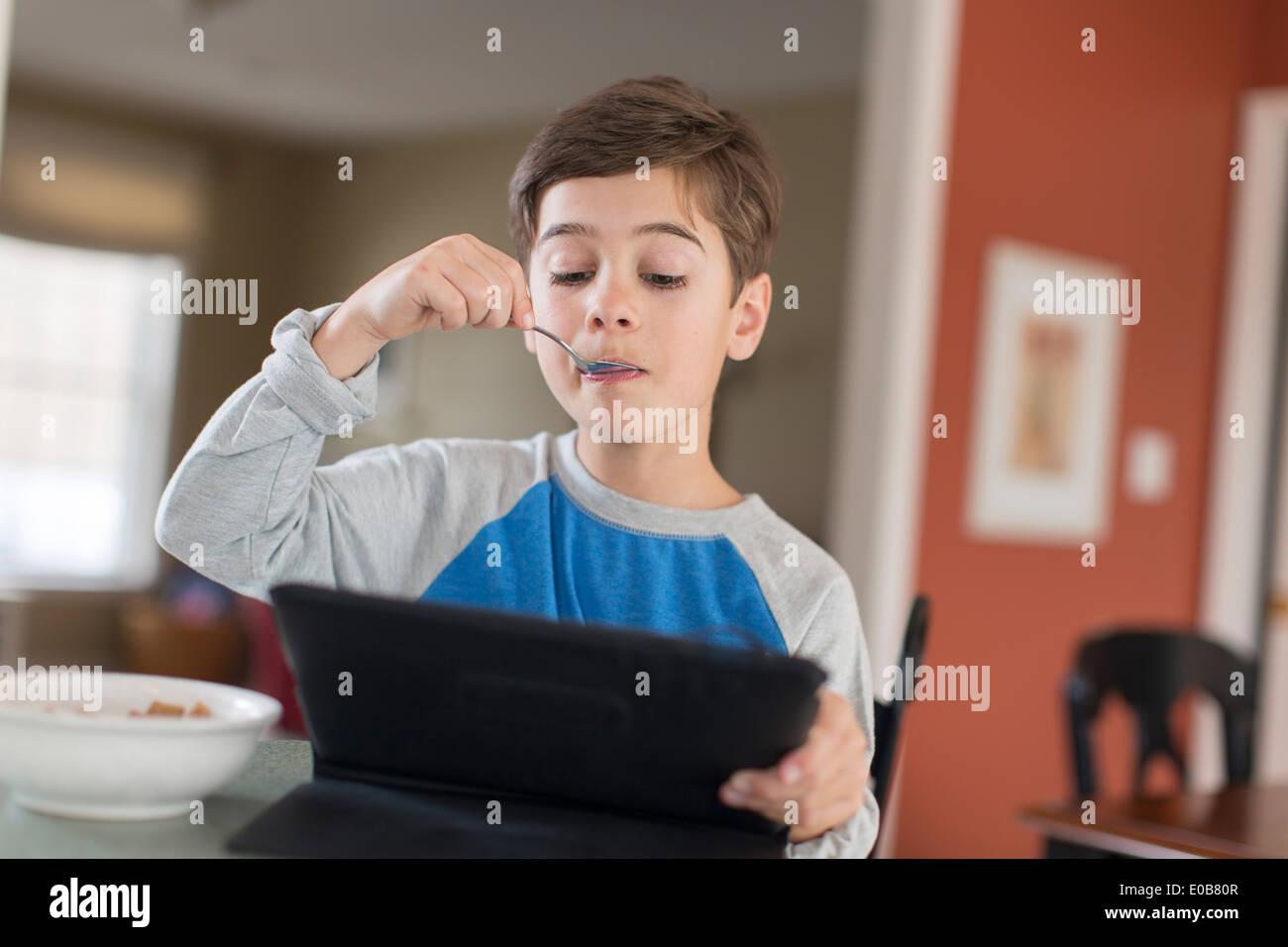 Ragazzo che guarda a tavoletta digitale mentre si mangia la colazione Immagini Stock
