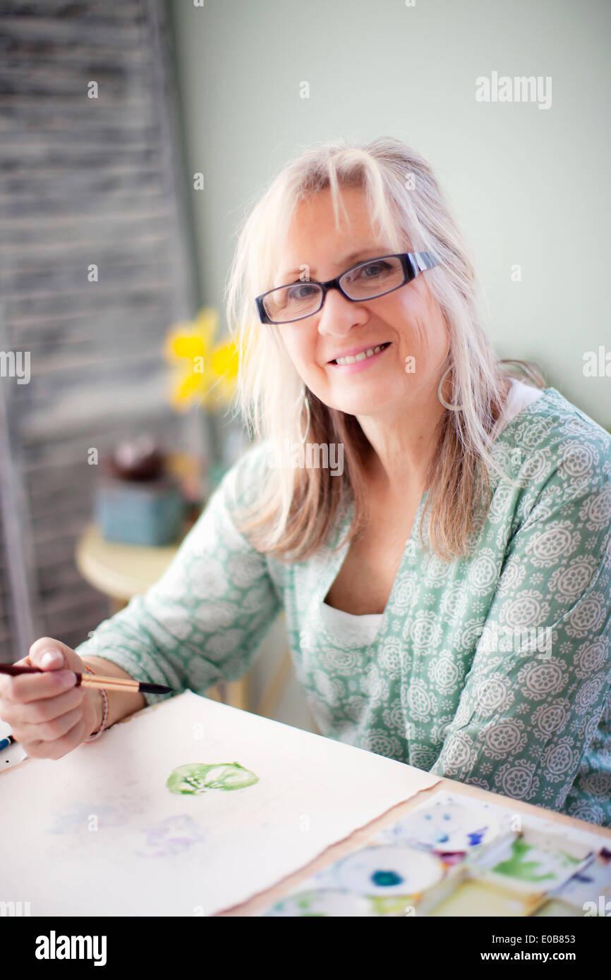Ritratto di femmina matura artista pittura ad acquerello in studio Immagini Stock