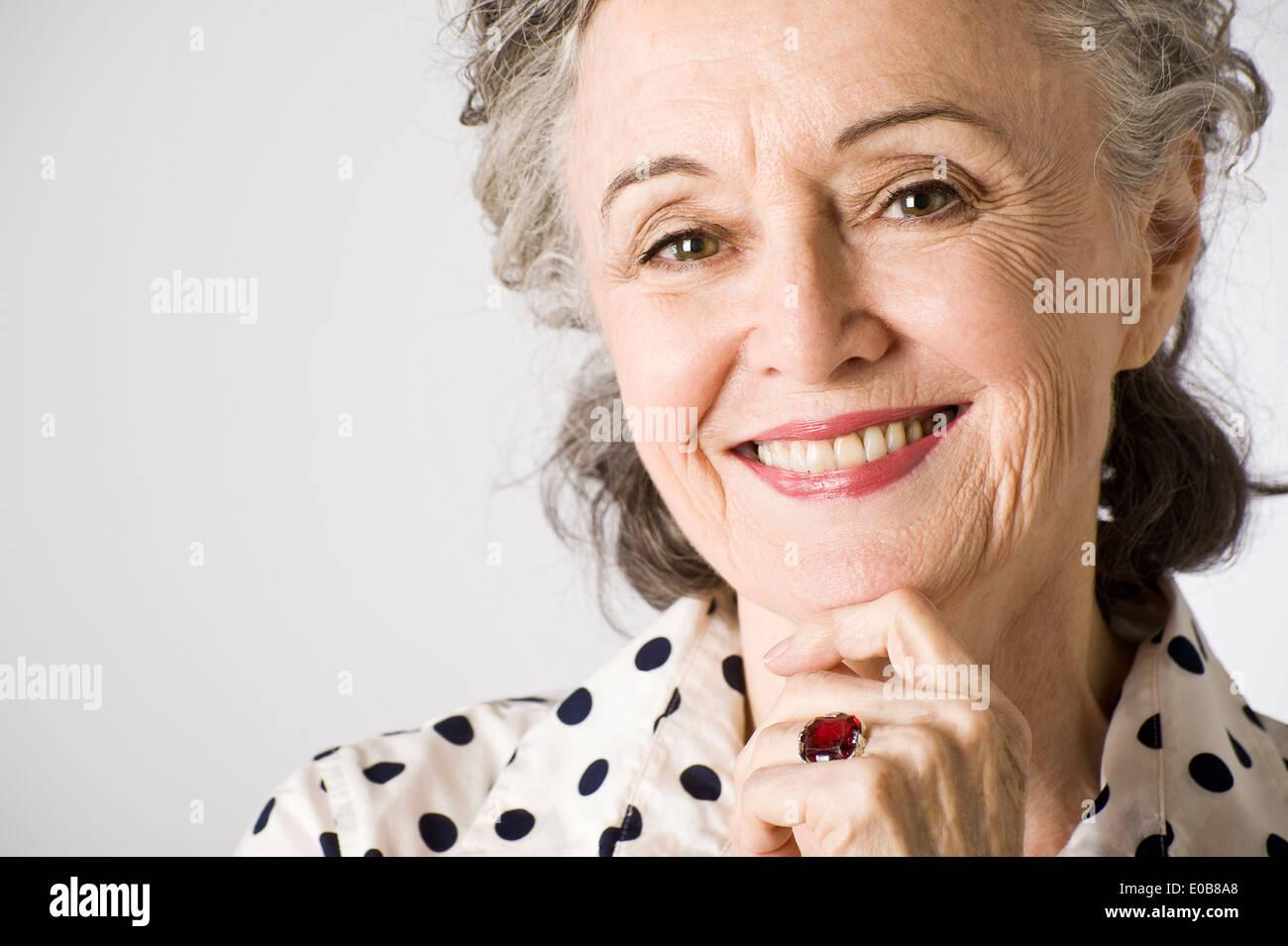 Ritratto di donna senior, mano sul mento, sorridente Immagini Stock