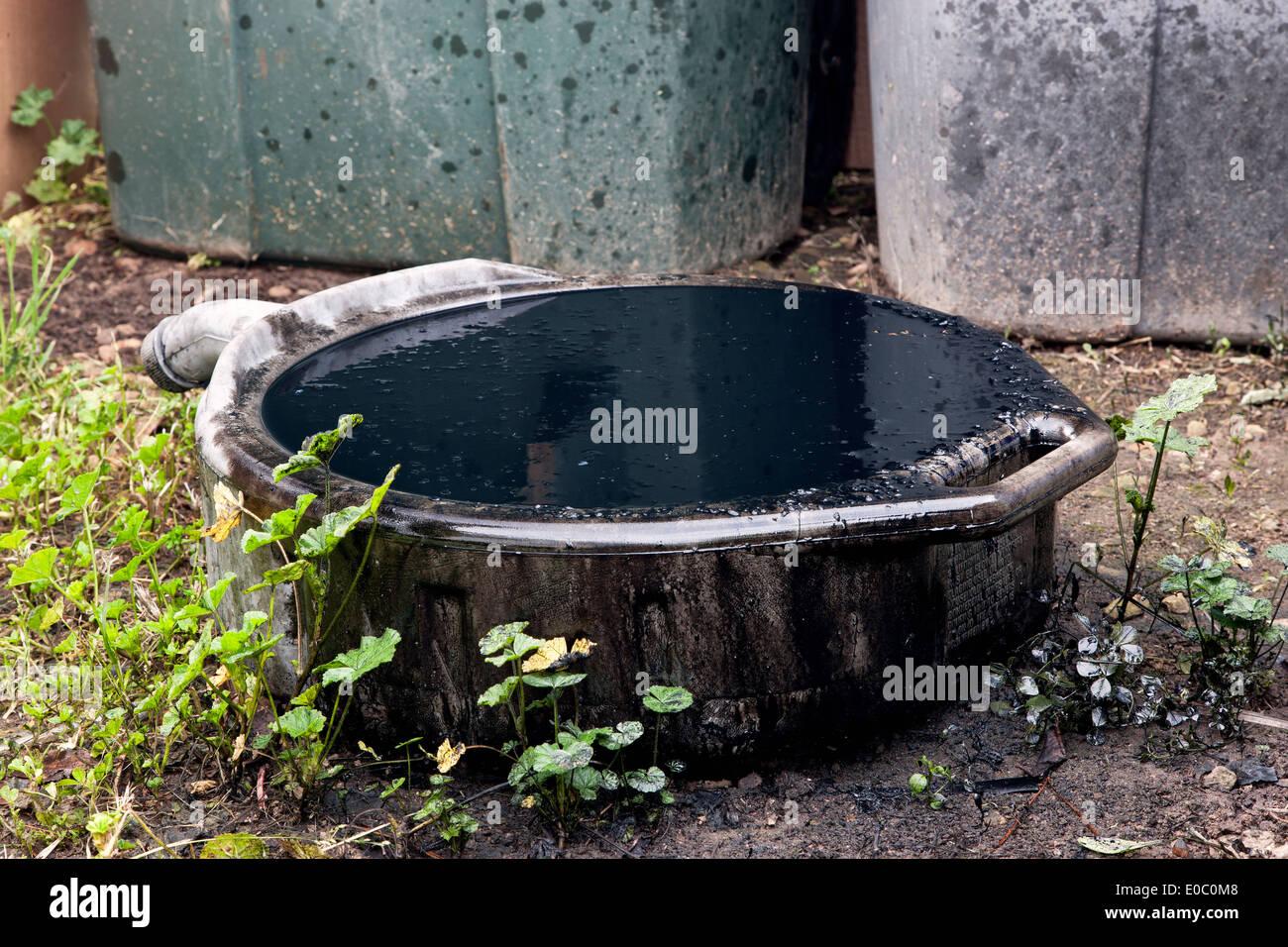 Vaschetta di scarico olio fuoriuscite, traboccante contenente sporco di olio motore. Immagini Stock