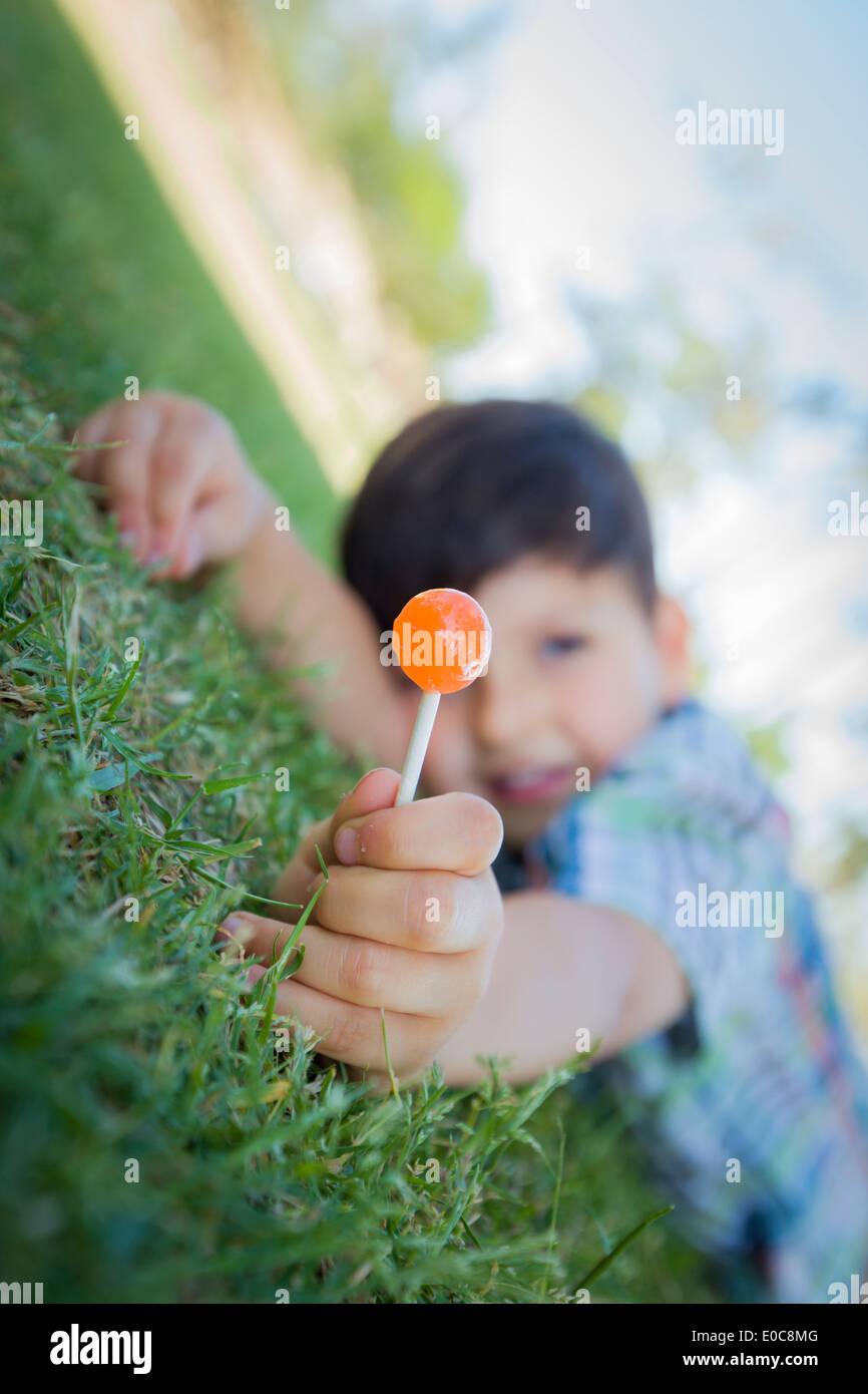 Bel giovane ragazzo godendo il suo Lollipop all'aperto sull'erba. Immagini Stock