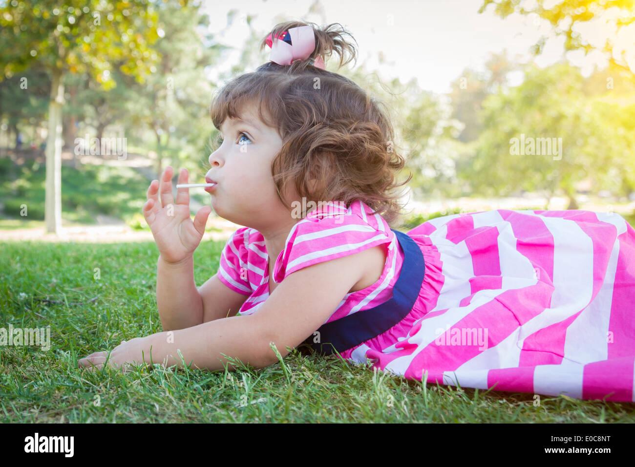 Carino Bambina godendo della sua Lollipop all'esterno. Immagini Stock