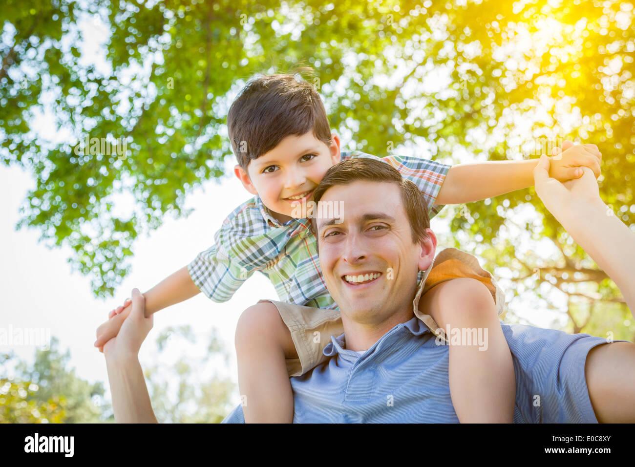Razza mista padre e figlio giocando Piggyback insieme nel parco. Immagini Stock