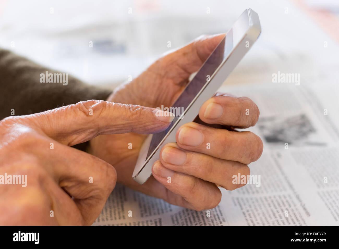 Femmina scrittura matura il telefono cellulare in luoghi chiusi closeup Immagini Stock