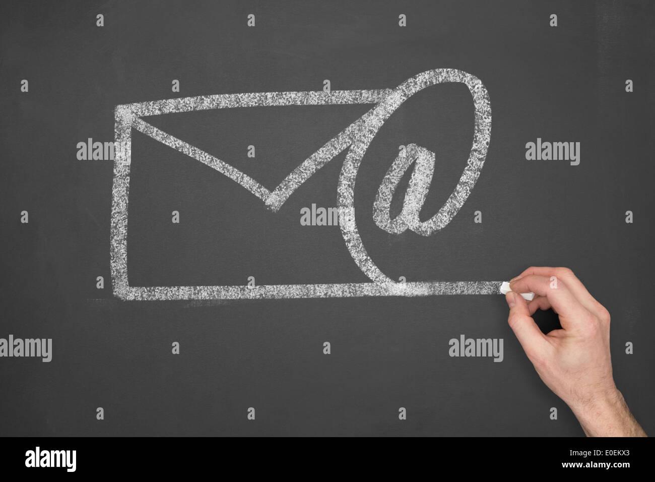 Un imprenditore il disegno di un simbolo di posta elettronica su una lavagna. Immagini Stock