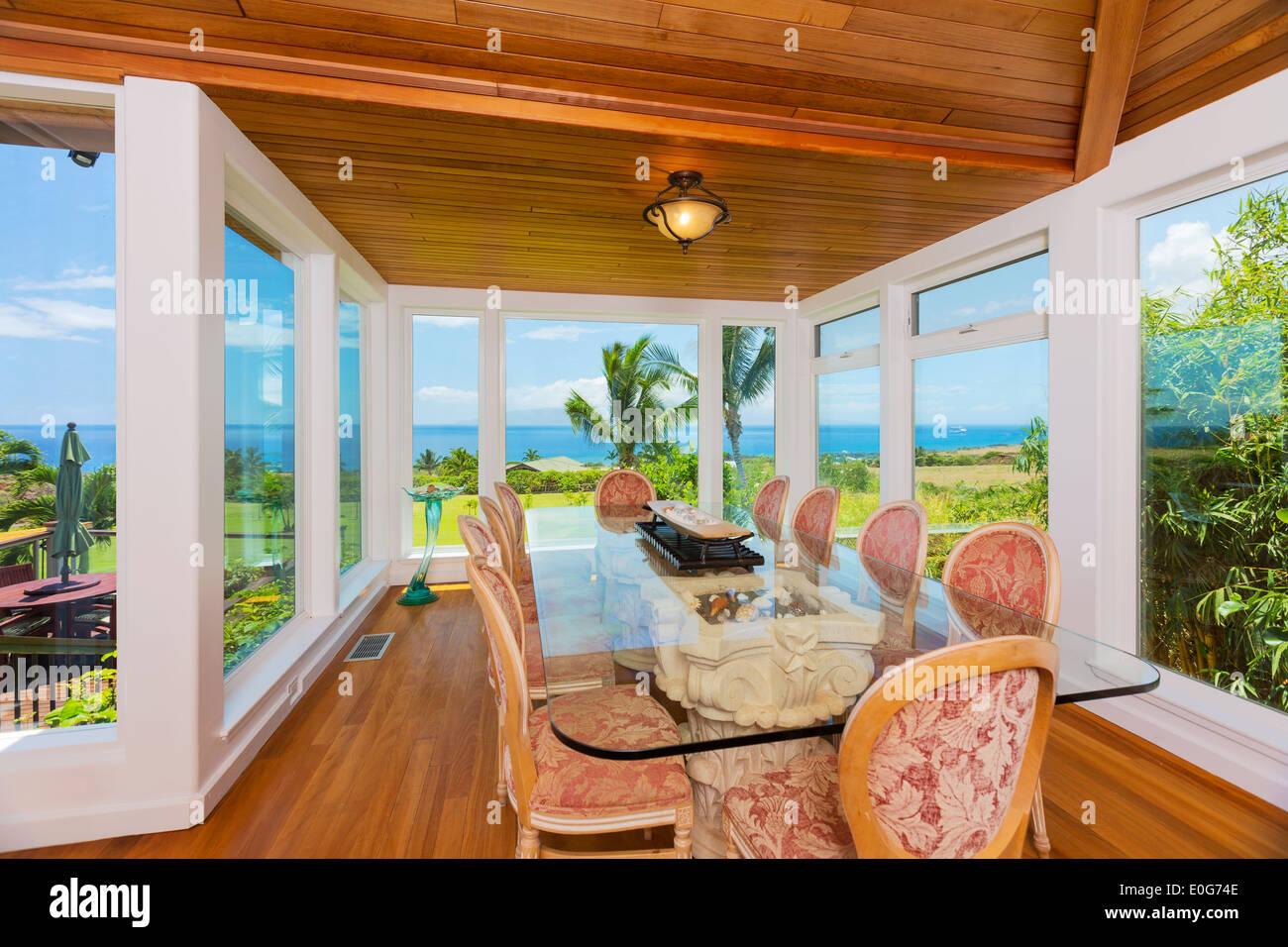 Sala da pranzo con grandi finestre e pavimento in legno duro in casa di lusso Immagini Stock