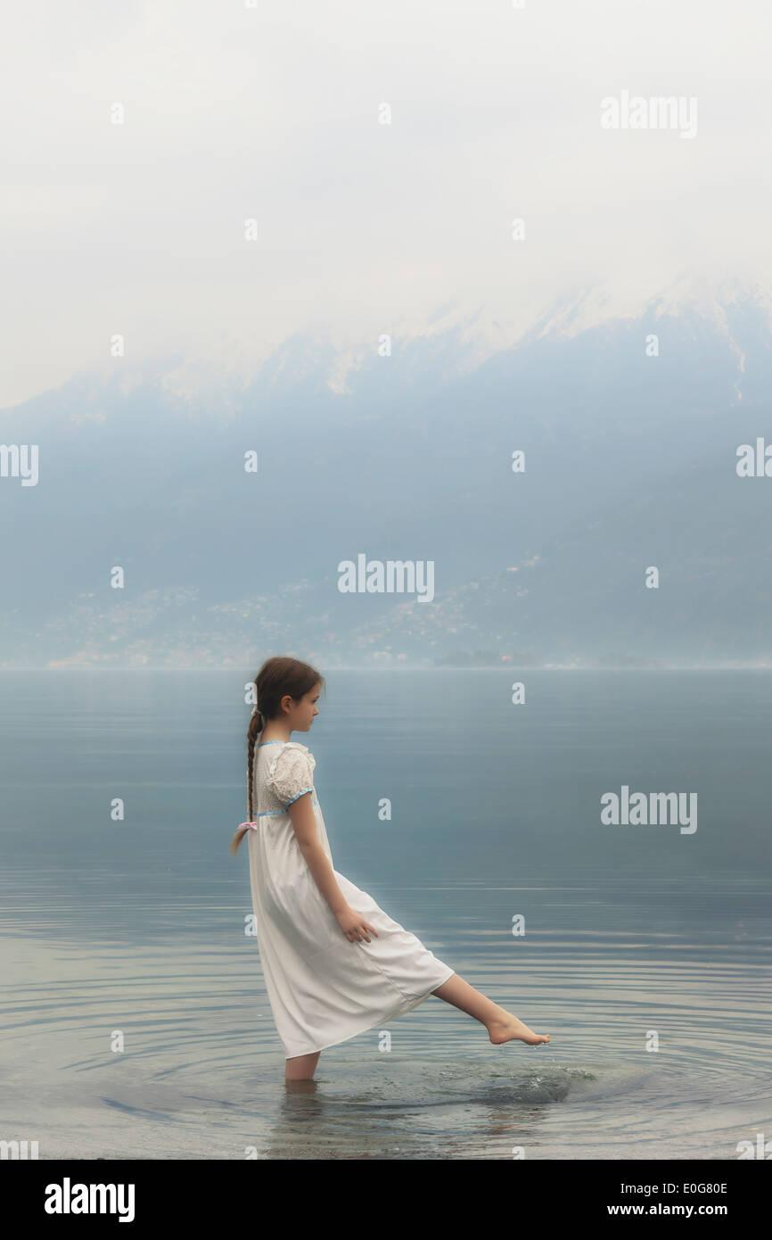 Una ragazza in un abito è in piedi in un lago Immagini Stock
