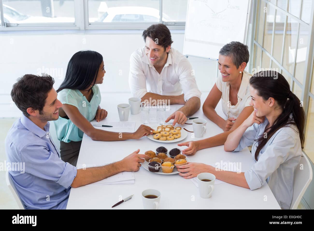 La gente di affari chattare mentre muffin mangiare e bere caffè Immagini Stock