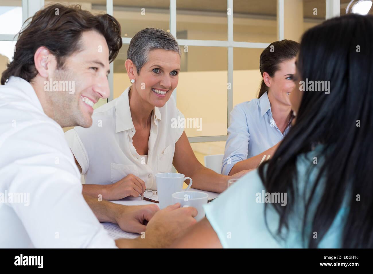 La gente di affari sorriso e chattare mentre godendo bevande calde Immagini Stock