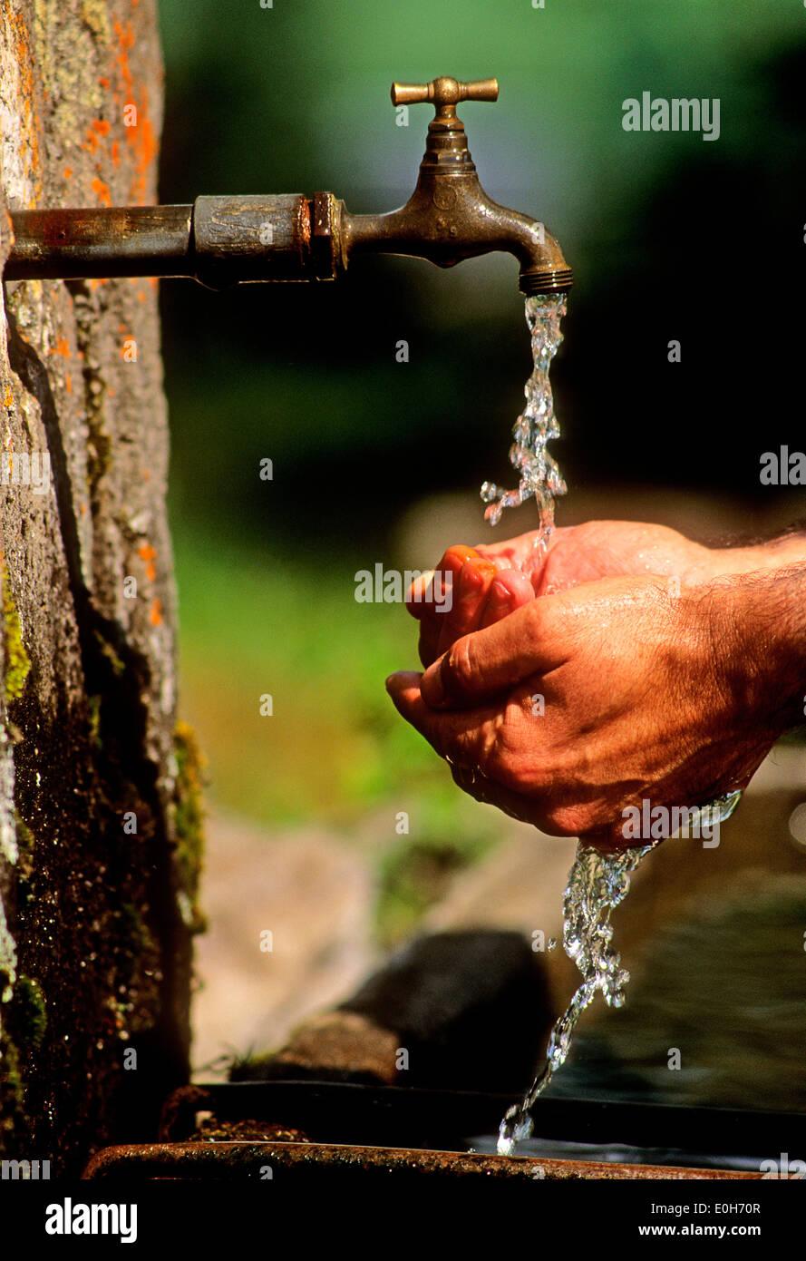 Lavaggio delle mani in corrispondenza di un rubinetto esterno nel giardino Immagini Stock
