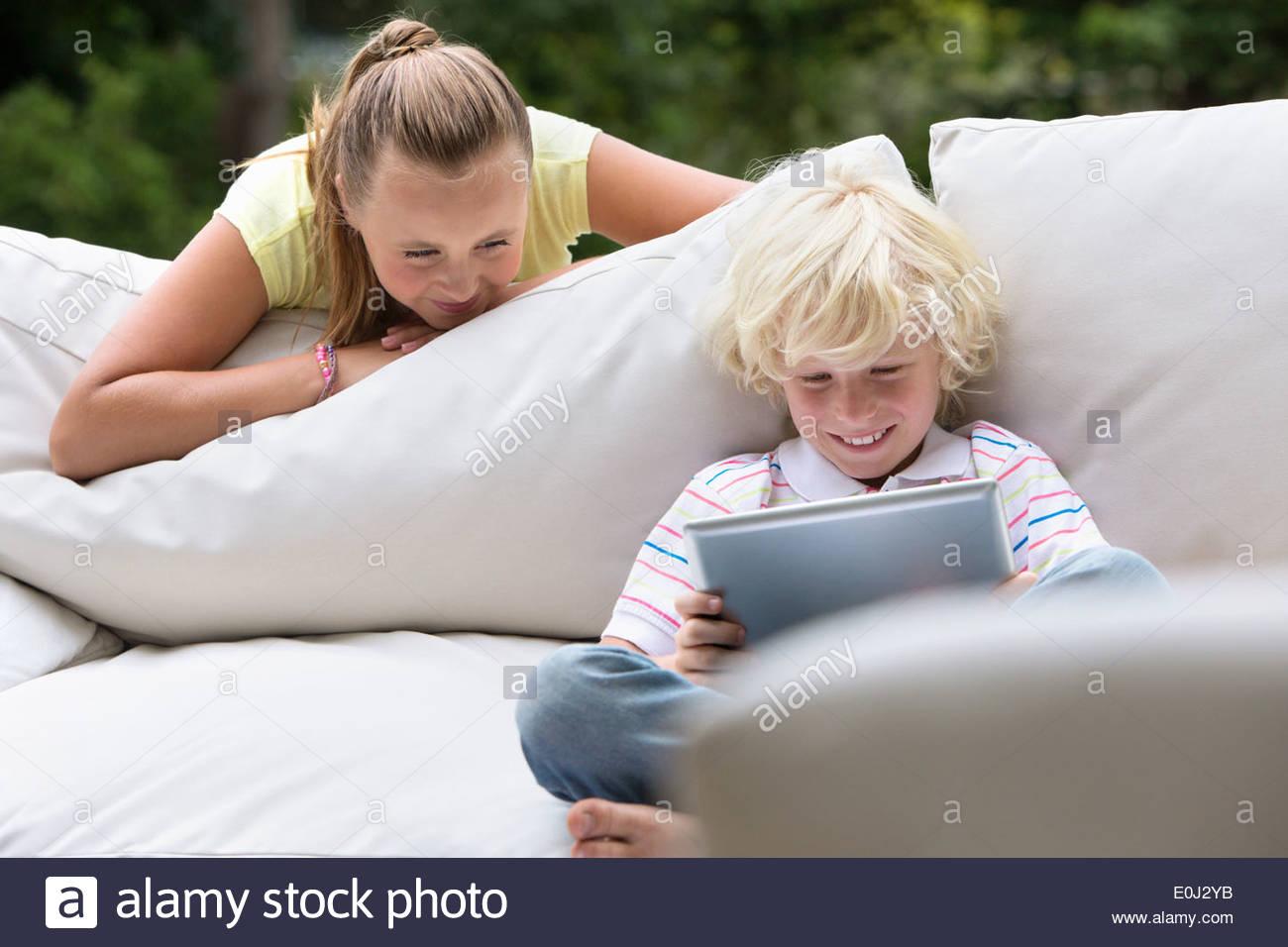 Suor guardando il fratello con tavoletta digitale sul divano per esterni Immagini Stock