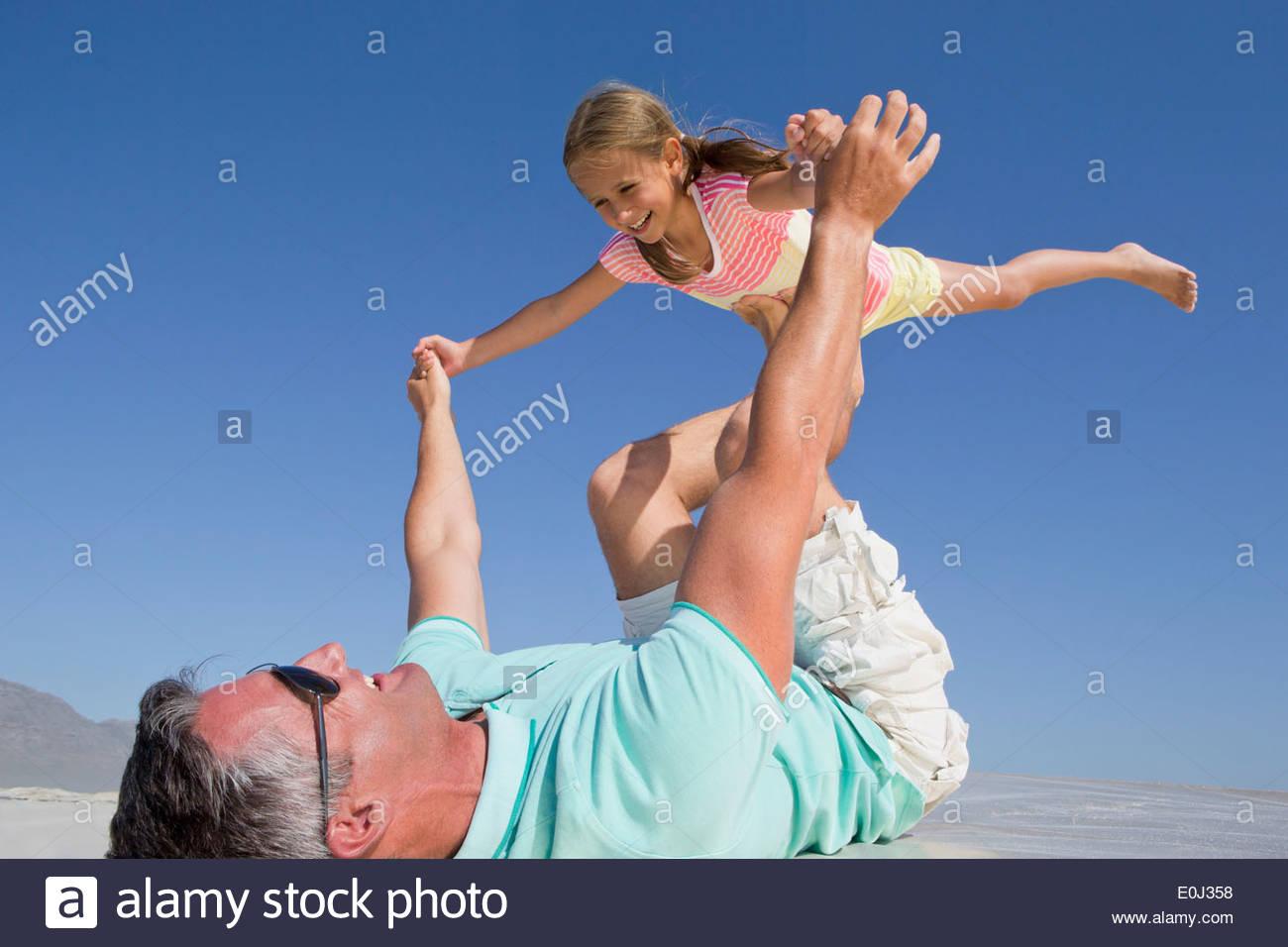Padre figlia di sollevamento di sunny beach Immagini Stock