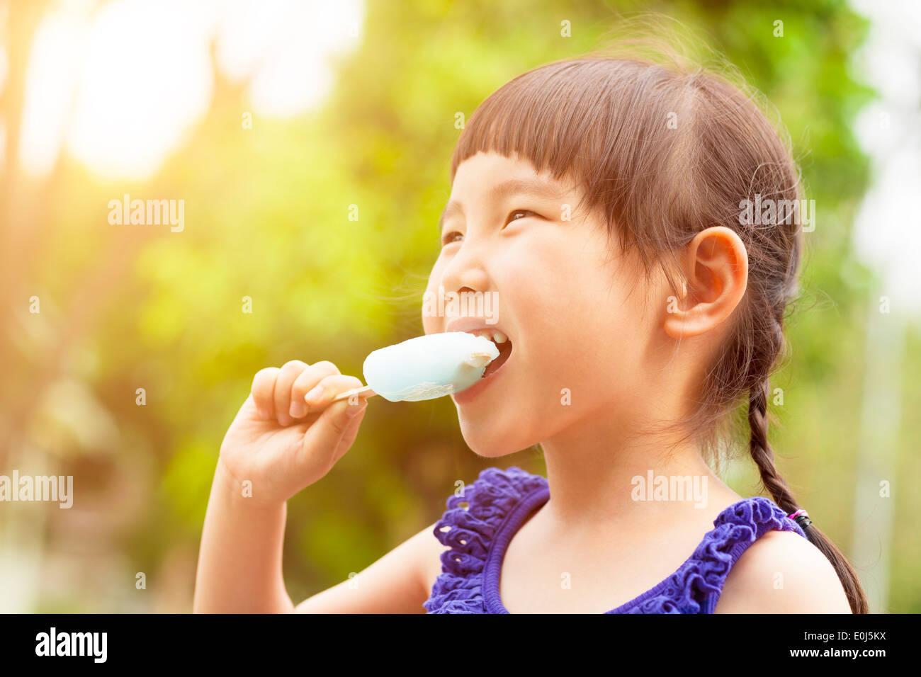 Felice bambina mangiare ghiaccioli in estate con il tramonto del sole Foto Stock