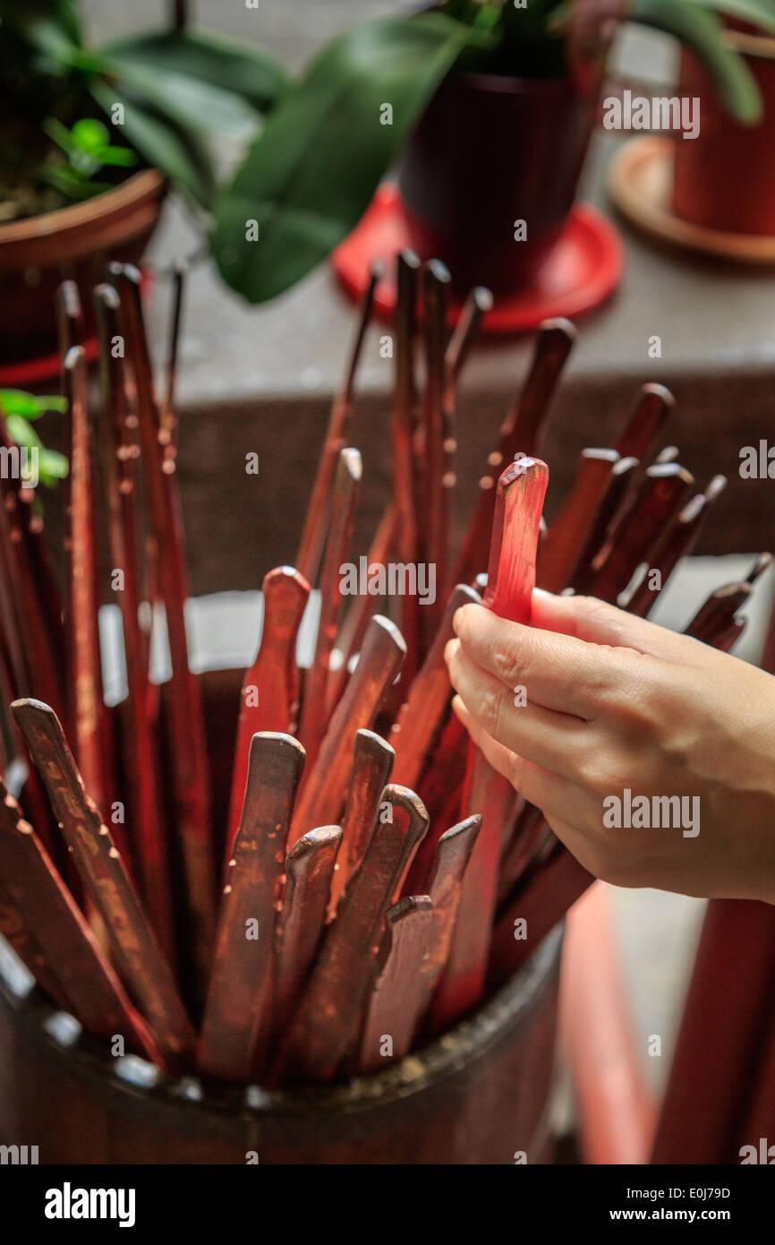La mano di una donna picking fortune raccontando bastoni Immagini Stock