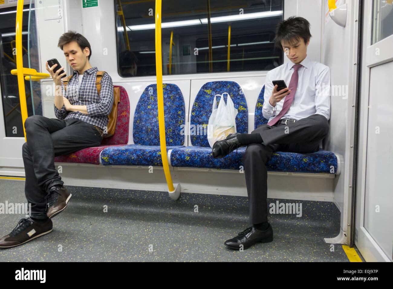 Sydney Australia NSW Nuovo Galles del Sud i treni City Circle i mezzi di trasporto pubblici a bordo i piloti in cabina passeggeri uomo asiatico alla ricerca di messaggi dello smartphone co Immagini Stock