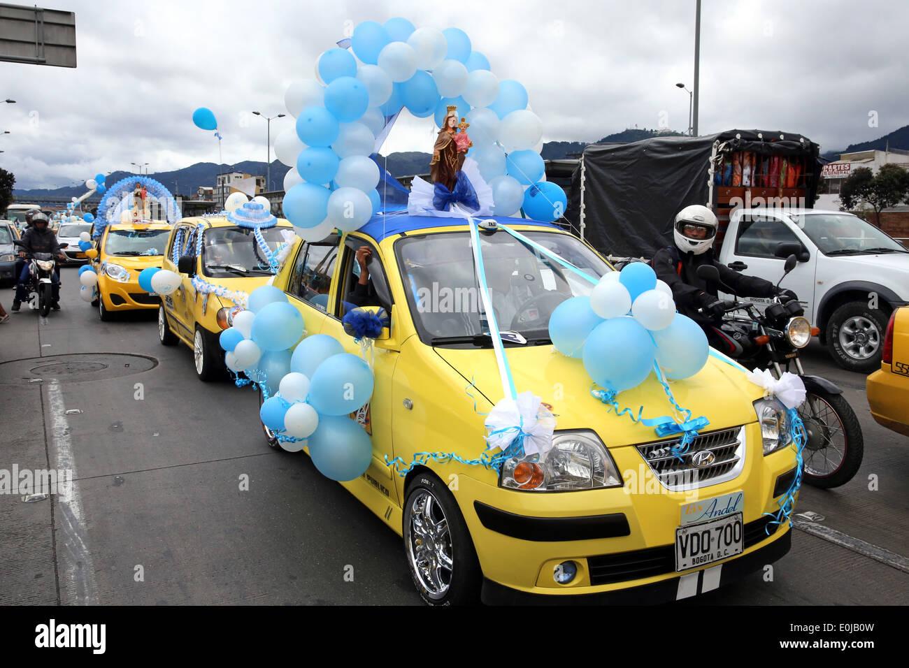 Sfilata di taxi decorato con palloncini e statue di Madre Maria per onorare la madre di Gesù Cristo. Bogotà, Colombia Immagini Stock