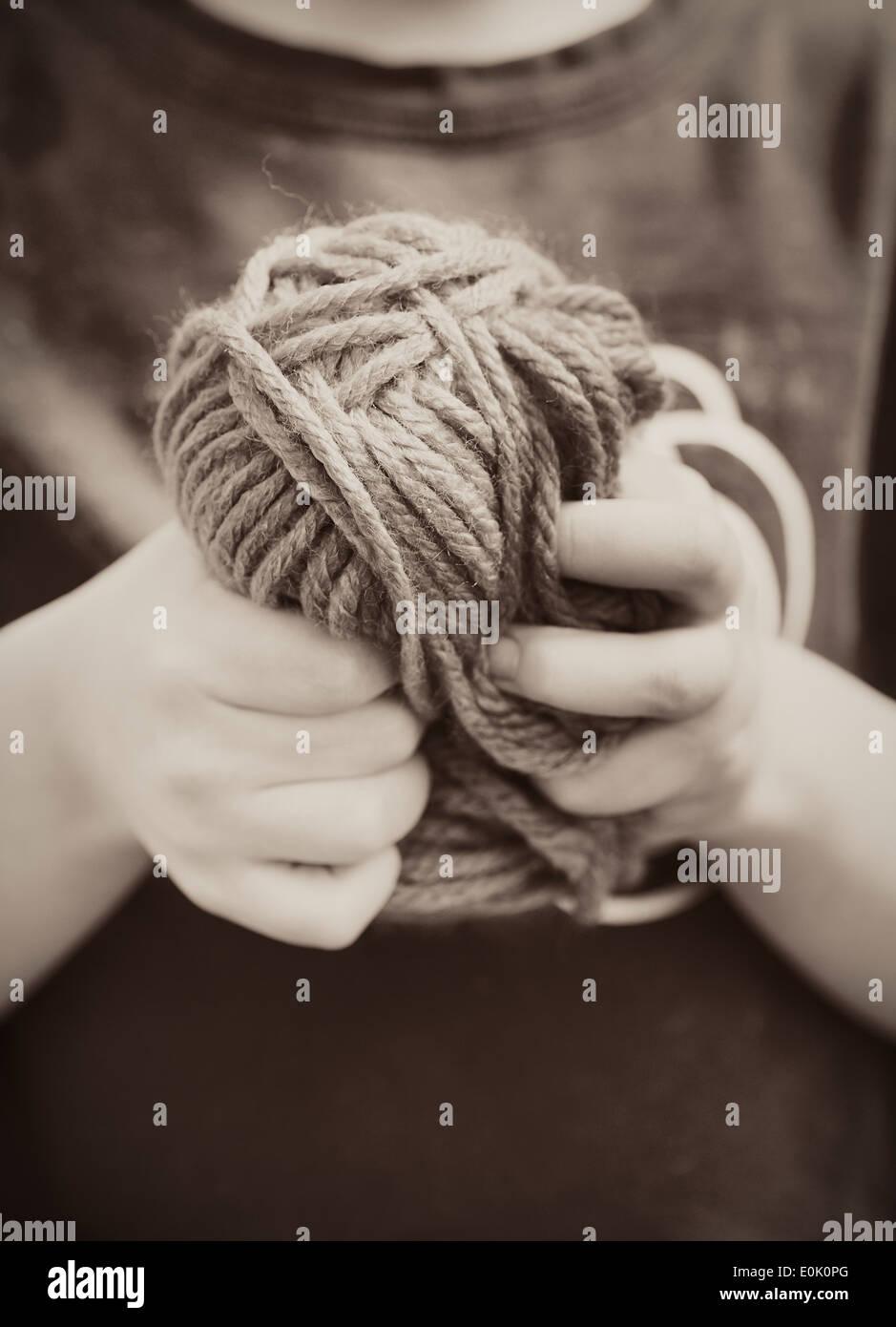 Close up della bambina tenendo una palla di filato nelle sue mani Immagini Stock