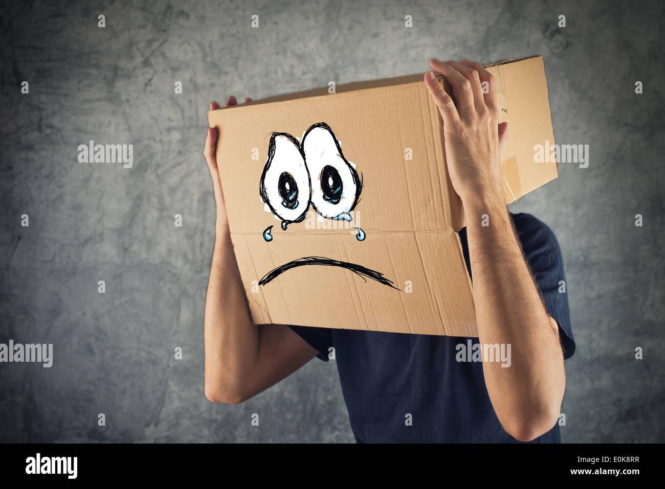Uomo con scatola di cartone sulla sua testa e tristi lacrime di espressione. Concetto di tristezza e depressione. Immagini Stock