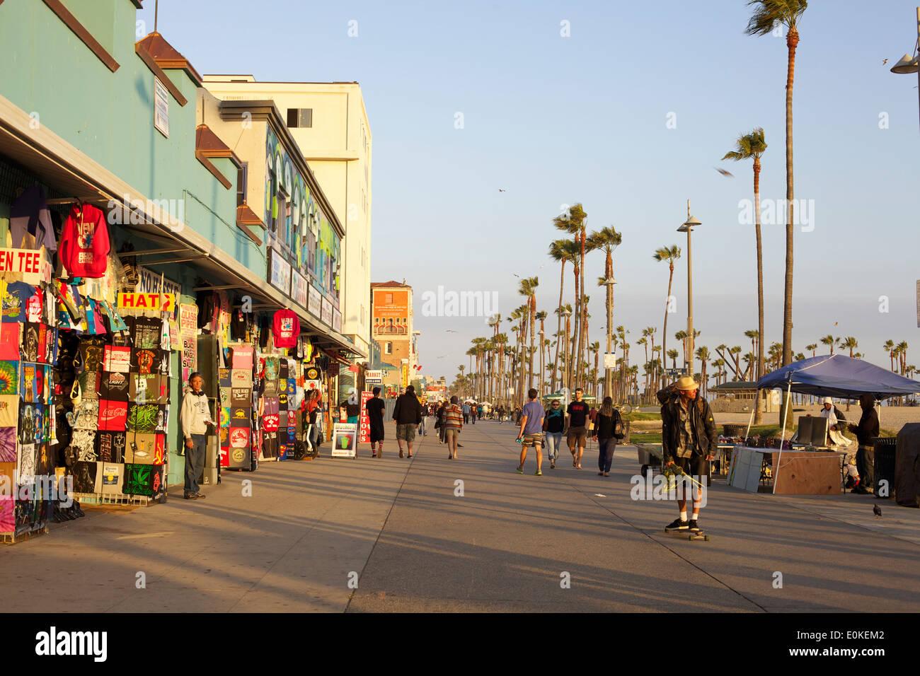 Gli amanti dello shopping a piedi e un giovane uomo di skateboard giù il Sunny Venice Beach Boardwalk in Los Angeles, Foto Stock