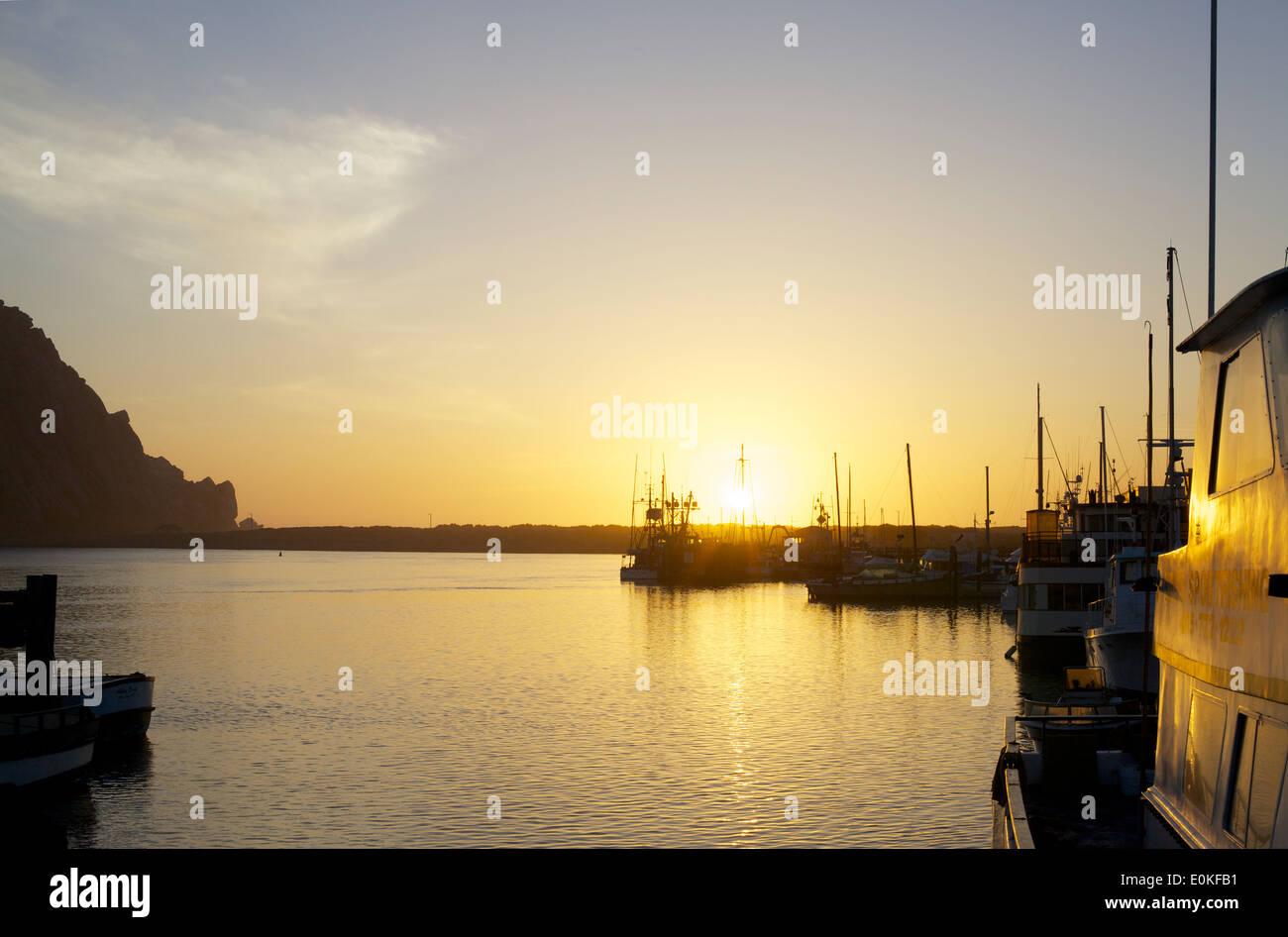 Barche di galleggiare sull'acqua come il sole tramonta sull'orizzonte a Morro Bay, California. Immagini Stock