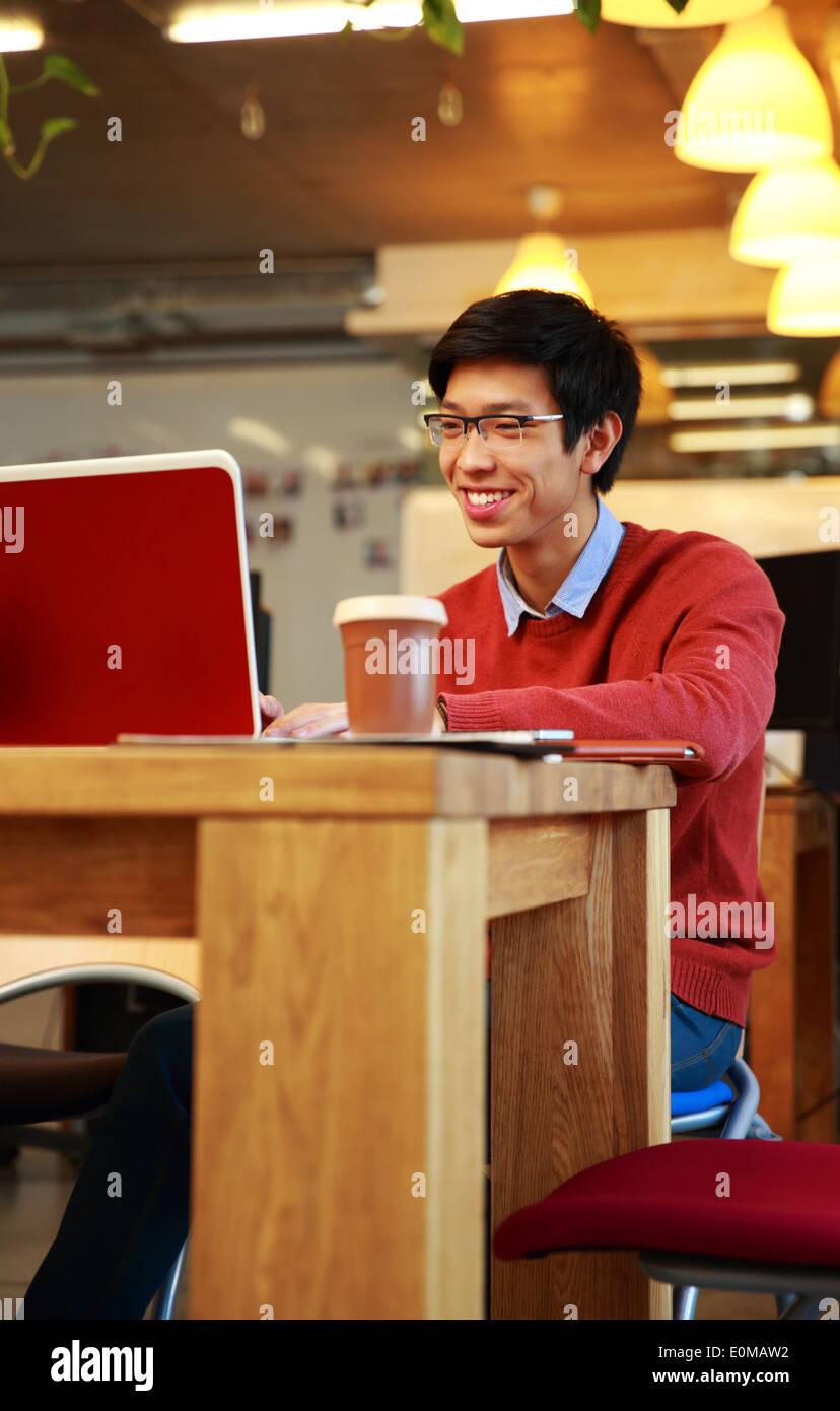 Sorridente uomo asiatico in bicchieri lavorando sul computer portatile Immagini Stock