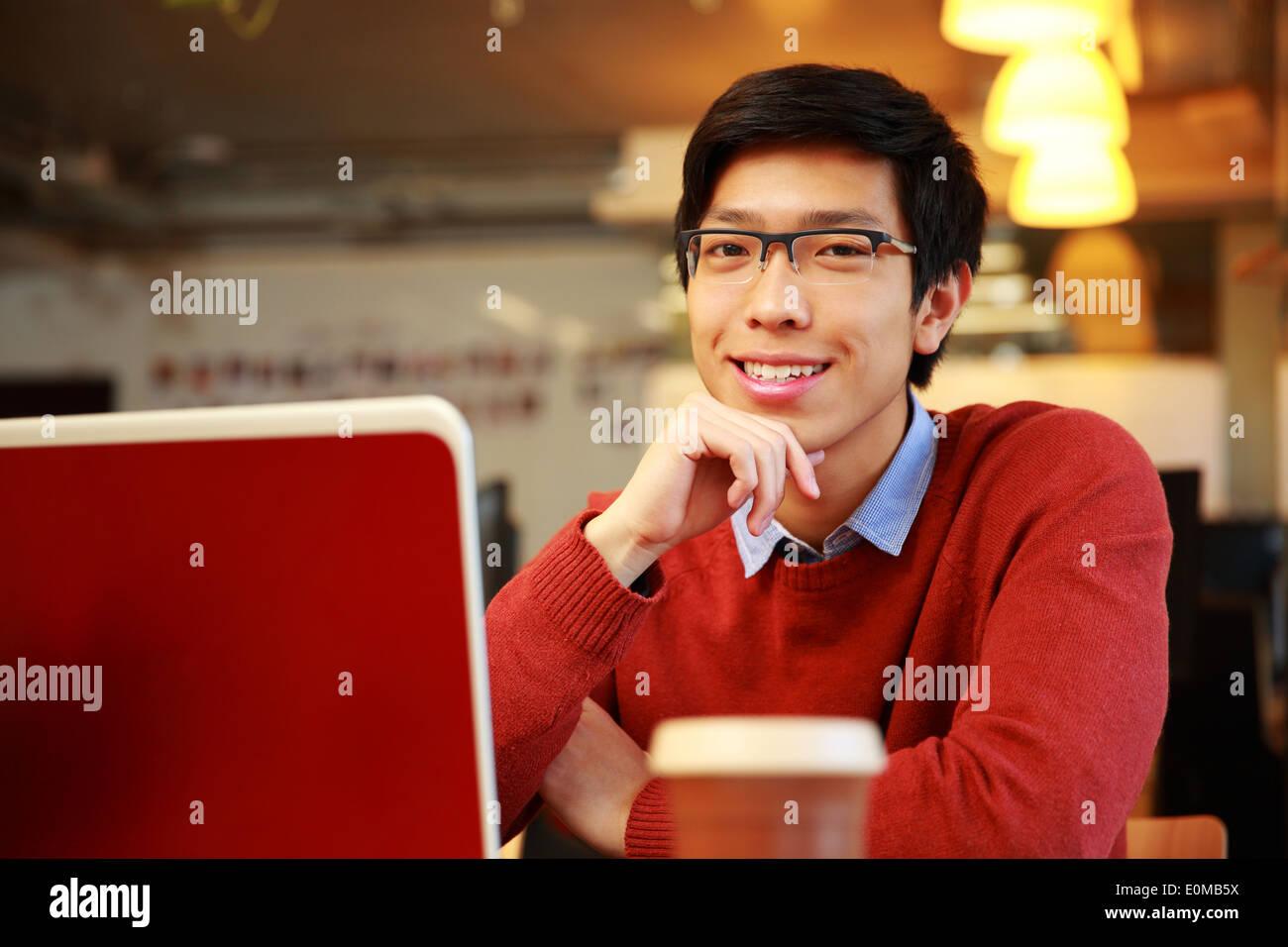 Allegro uomo asiatico di sedere a tavola con laptop e guardando la fotocamera Immagini Stock