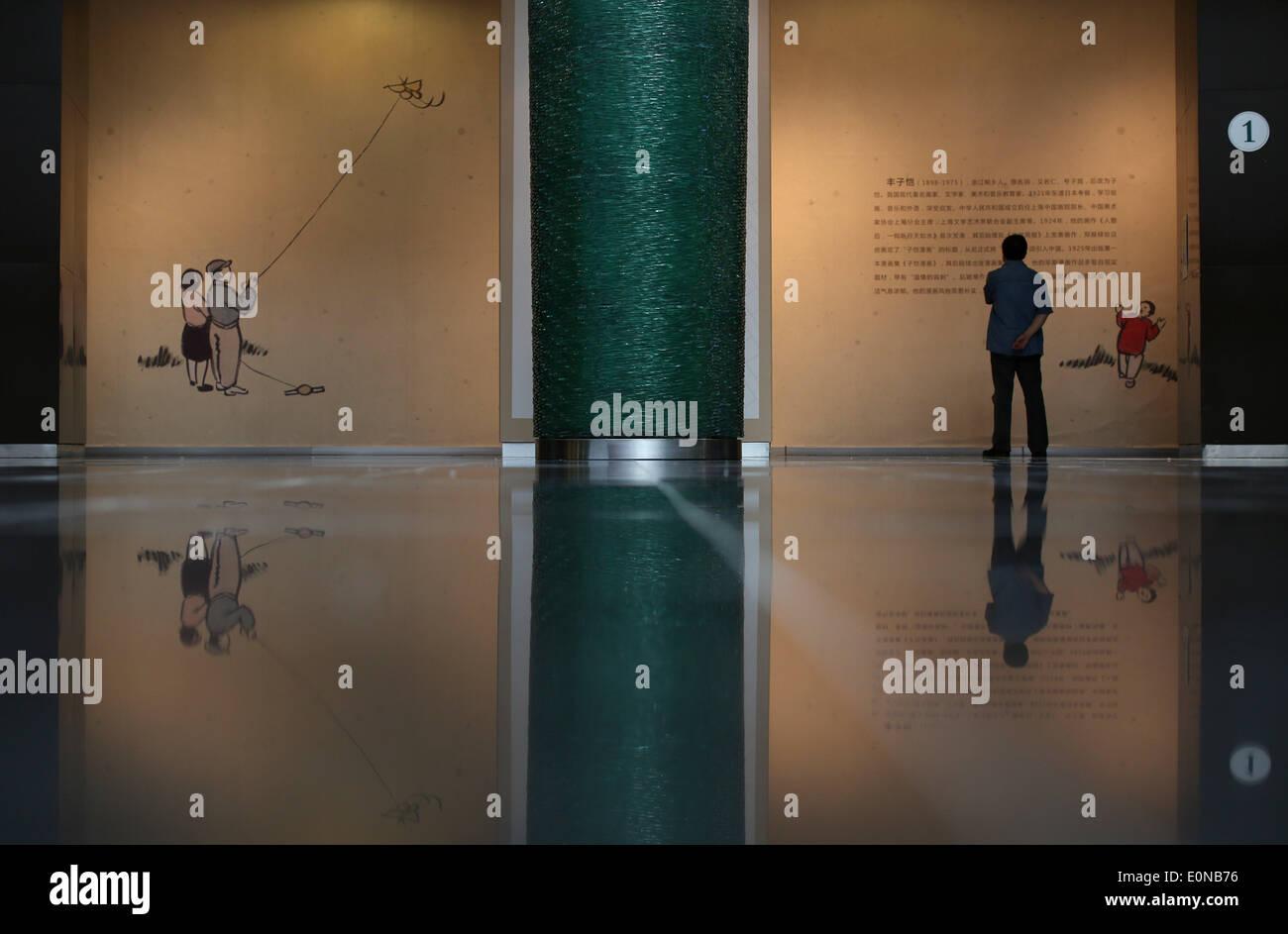 Shenyang, cinese della provincia di Liaoning. 16 Maggio, 2014. Un uomo guarda le opere di Feng Zikai, un famoso fumettista cinese, durante l'anteprima di una mostra di Feng di opere d'arte di Shenyang, capitale del nord-est della Cina di provincia di Liaoning, 16 maggio 2014. La art show sarà aperto al pubblico il 18 maggio. © Yao Jianfeng/Xinhua/Alamy Live News Immagini Stock