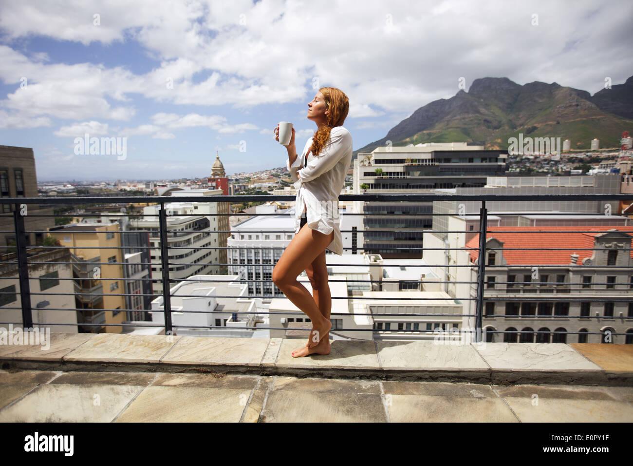 Giovane e bella donna che indossa una camicia solo in piedi sul balcone con tazza di caffè, godendo di Sun in un caldo giorno d'estate. Immagini Stock