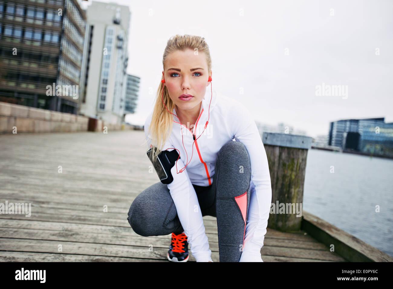 Donna Fitness sul Boardwalk accovacciato a legare il suo stringa guardando la fotocamera. Fiducioso giovane femmina la formazione del pareggiatore all'esterno. Immagini Stock