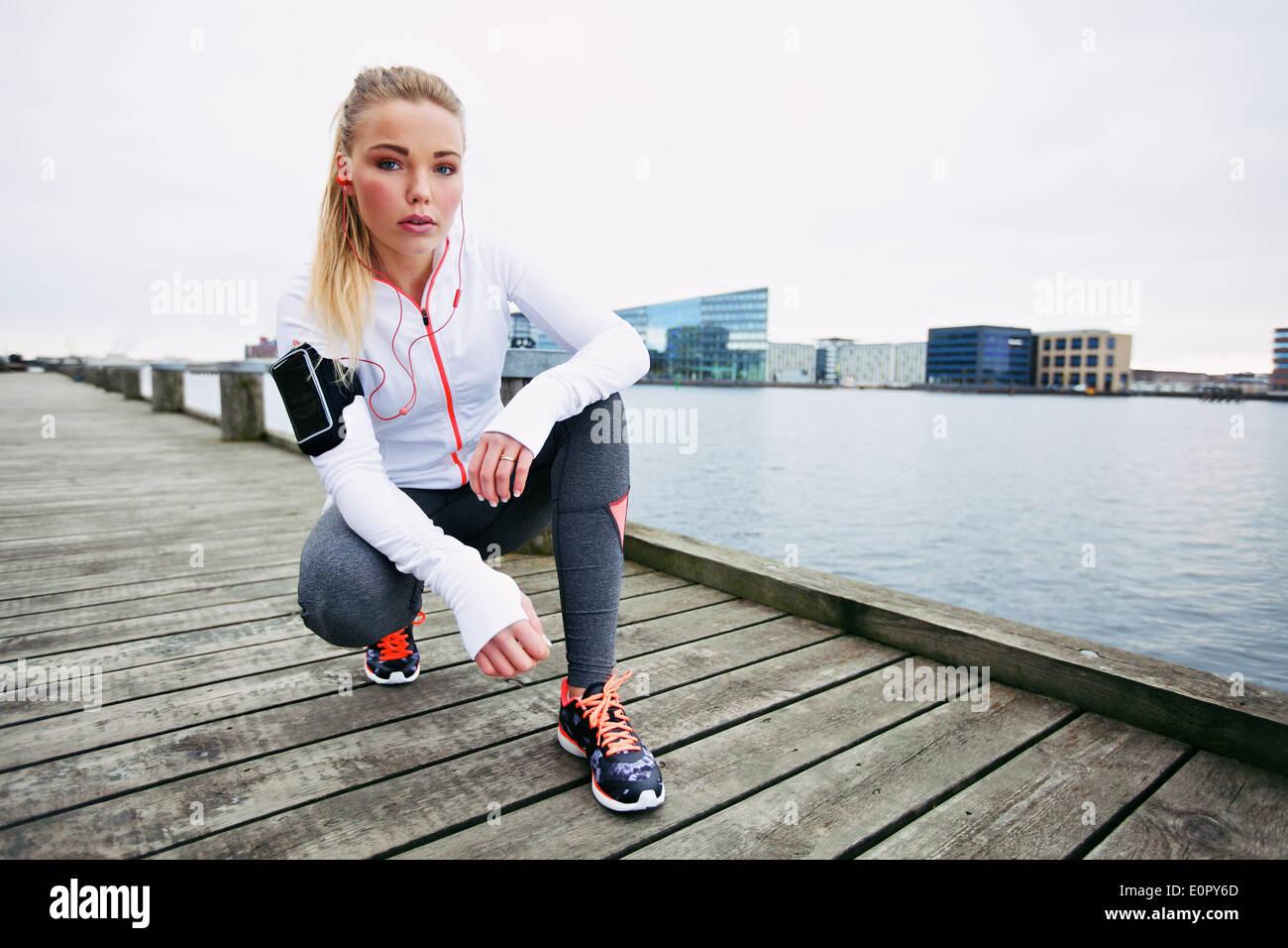 Giovane donna runner riposo dopo la esecuzione di allenamento. Femmina modello fitness accovacciato sul marciapiede lungo il fiume. Pareggiatore femmina di riposo. Immagini Stock