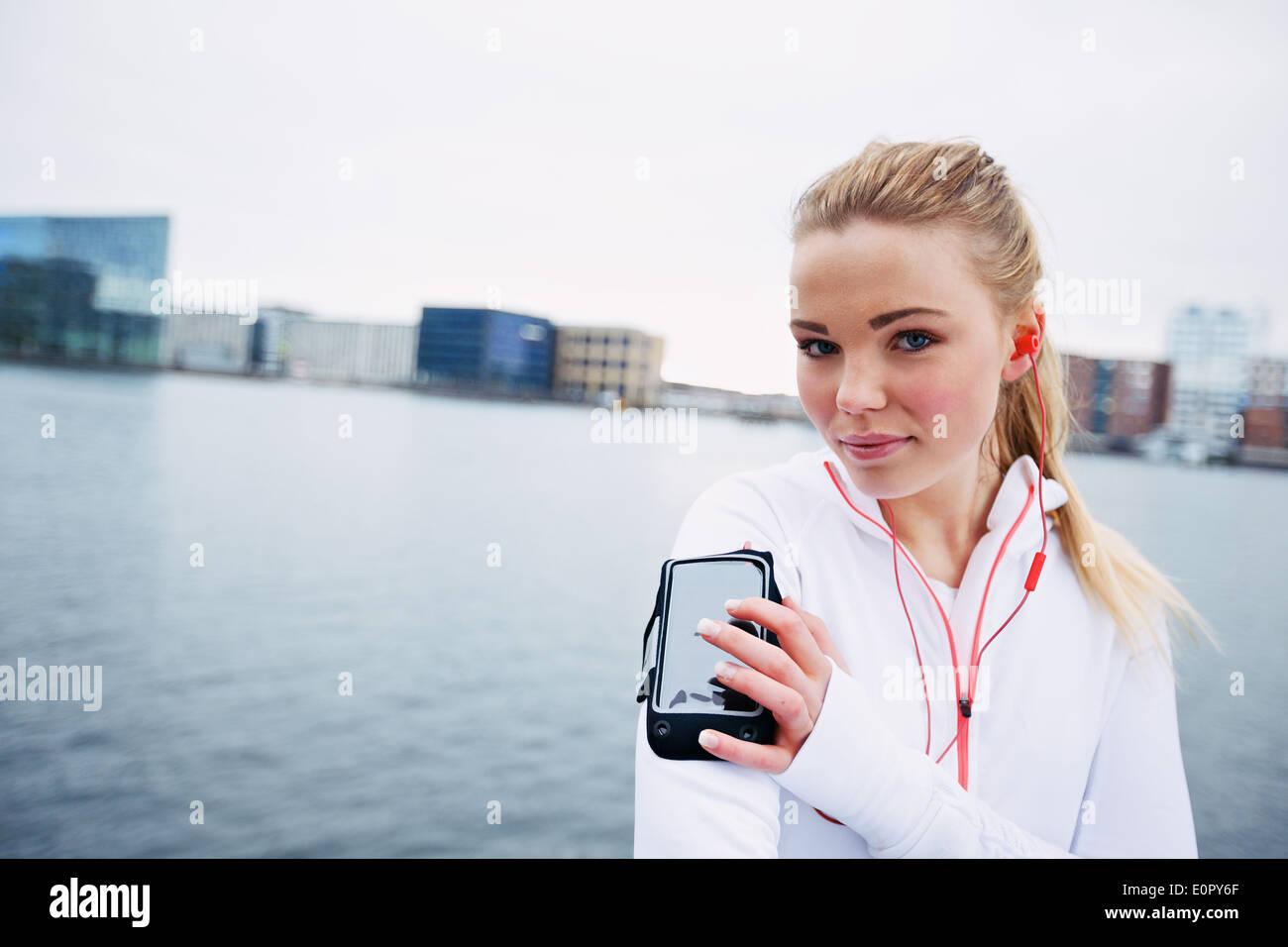 Atleta femminile della formazione all'aperto, utilizzando uno smartphone per monitorare i suoi progressi. Montare e sportività giovane atleta indossa fascia per il braccio Immagini Stock