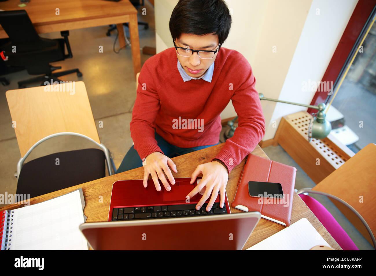 Giovane uomo asiatico in bicchieri lavorando sul computer portatile in ufficio Immagini Stock