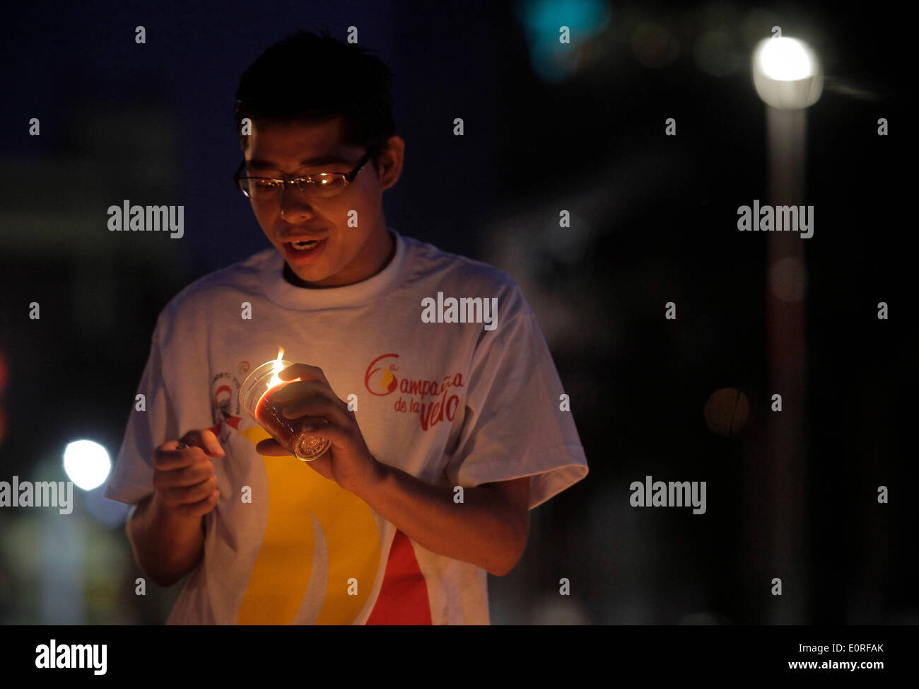 San Salvador El Salvador. 18 Maggio, 2014. Un residente accende una candela durante una commemorazione di persone morte di HIV/AIDS, in San Salvador, capitale di El Salvador, il 18 maggio 2014. Durante la commemorazione detenute da Atlacatl Vivo Asociation Positivo, 3.500 candele sono state accese al Divino Salvador del Mundo Square. © Oscar Rivera/Xinhua/Alamy Live News Immagini Stock