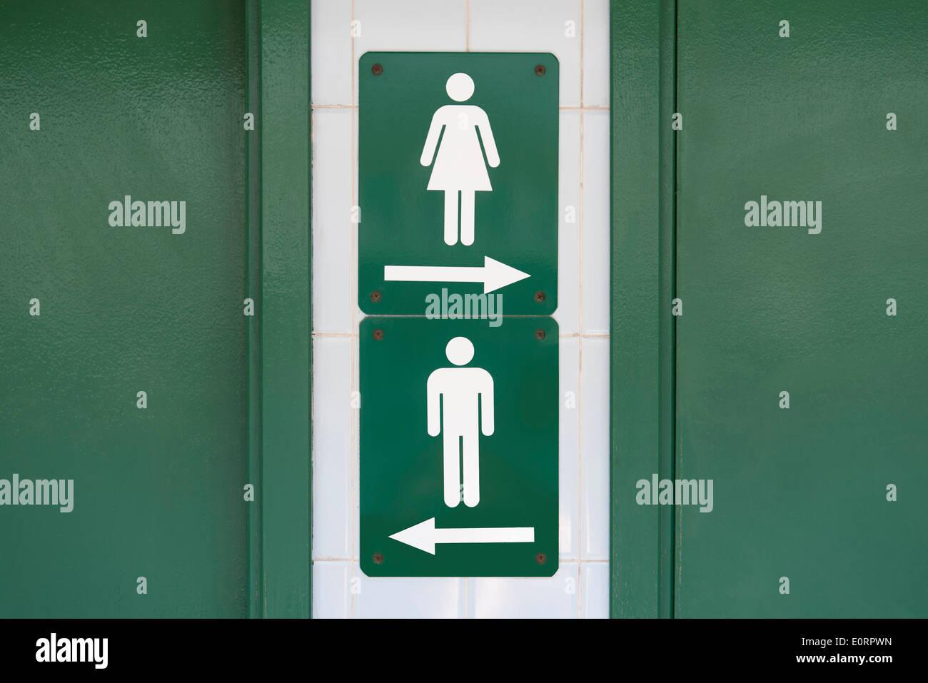Segno verde con maschio e femmina rivolta dei simboli per andare in direzioni opposte Immagini Stock