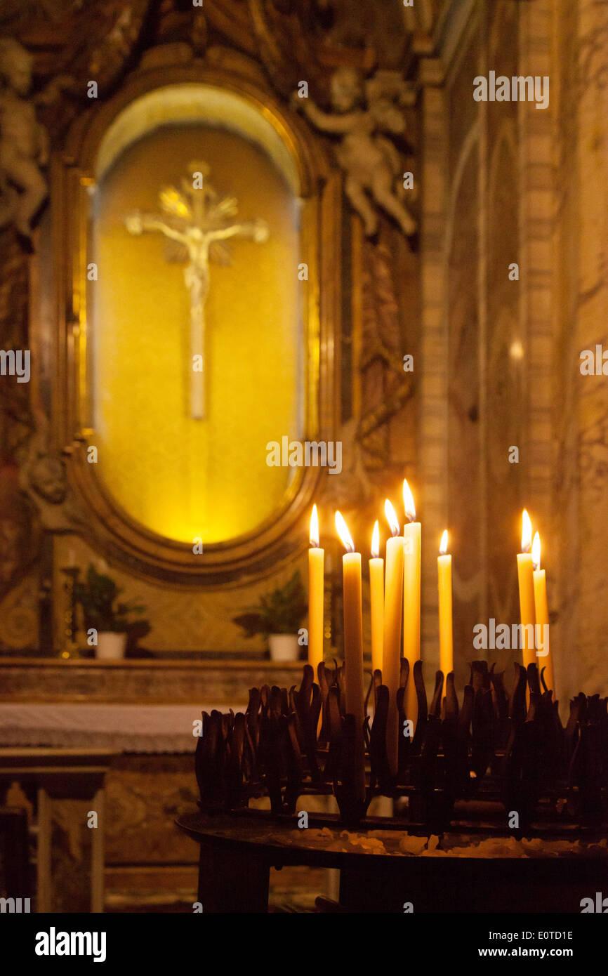 Candele di fronte a Gesù Cristo sulla croce, simboli religiosi del cristianesimo, Chiesa di Santa Maria Maddalena, Roma, Italia Immagini Stock