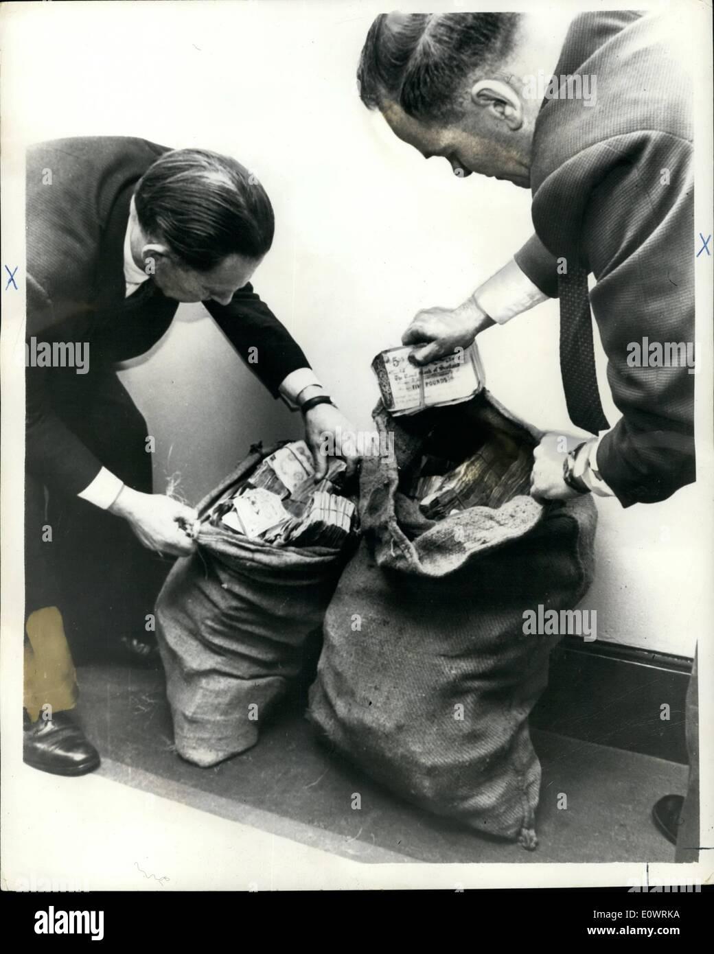 Il 12 Dic. 1963 - Treno rapina denaro trovato a Londra; due sporchi sacchi di patate contenente circa ~50.000 in ~5 e ~1 note rubati in la grande rapina in treno lo scorso agosto, sono stati trovati in un telefono nella parte sud di Londra dopo una chiamata telefonica di Scotland Yard. La foto mostra due detective controllando il denaro di Scotland Yard. (Da sinistra a destra) Det. Ispettore capo Syd Bradbury e Det. Inap Frank Williams. Foto Stock
