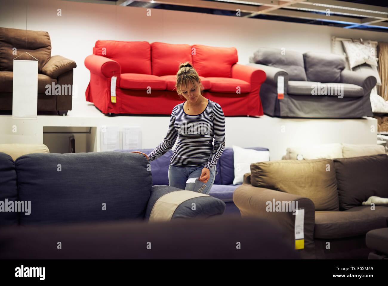 Giovane donna ispanica shopping per mobili, divano e home decor in negozio Immagini Stock
